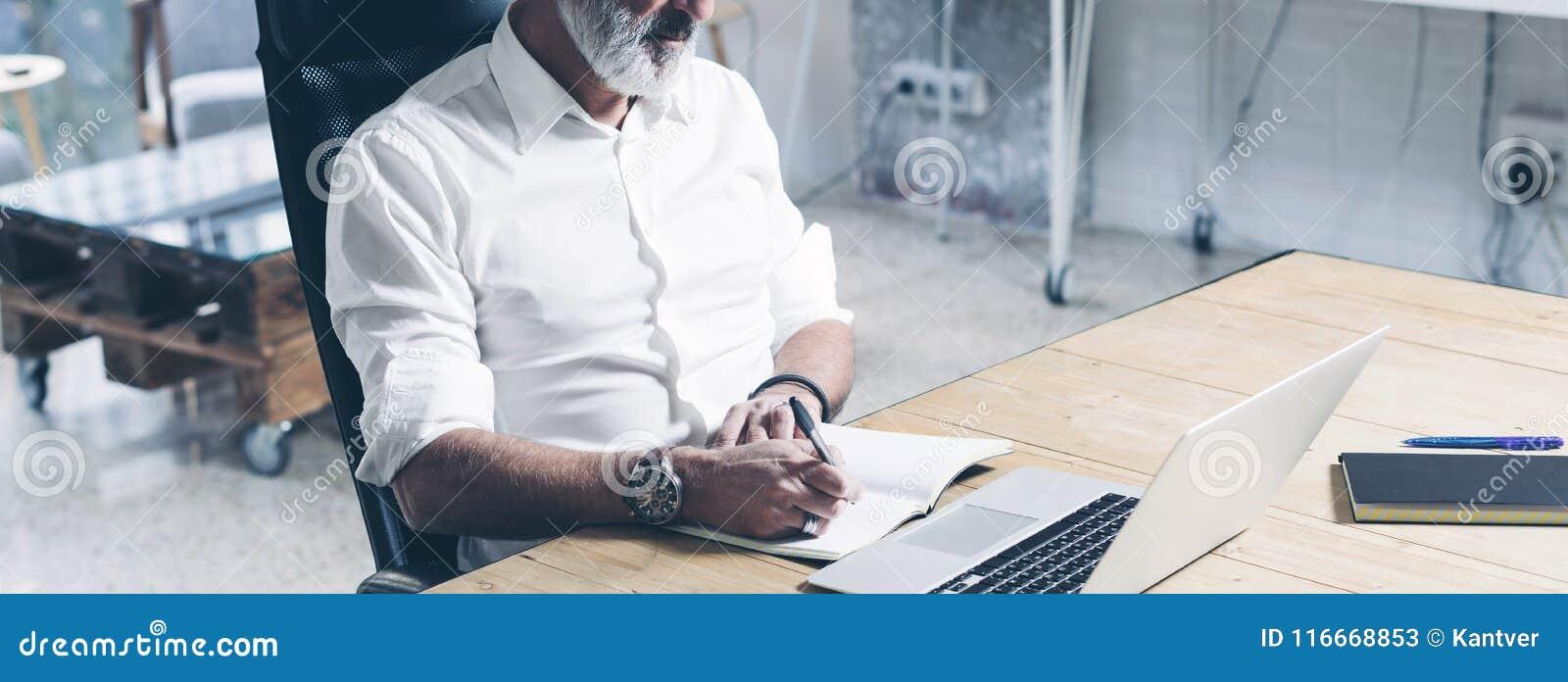 Attraktiver und vertraulicher erwachsener Geschäftsmann unter Verwendung der mobilen Laptop-Computers beim Arbeiten am Holztisch