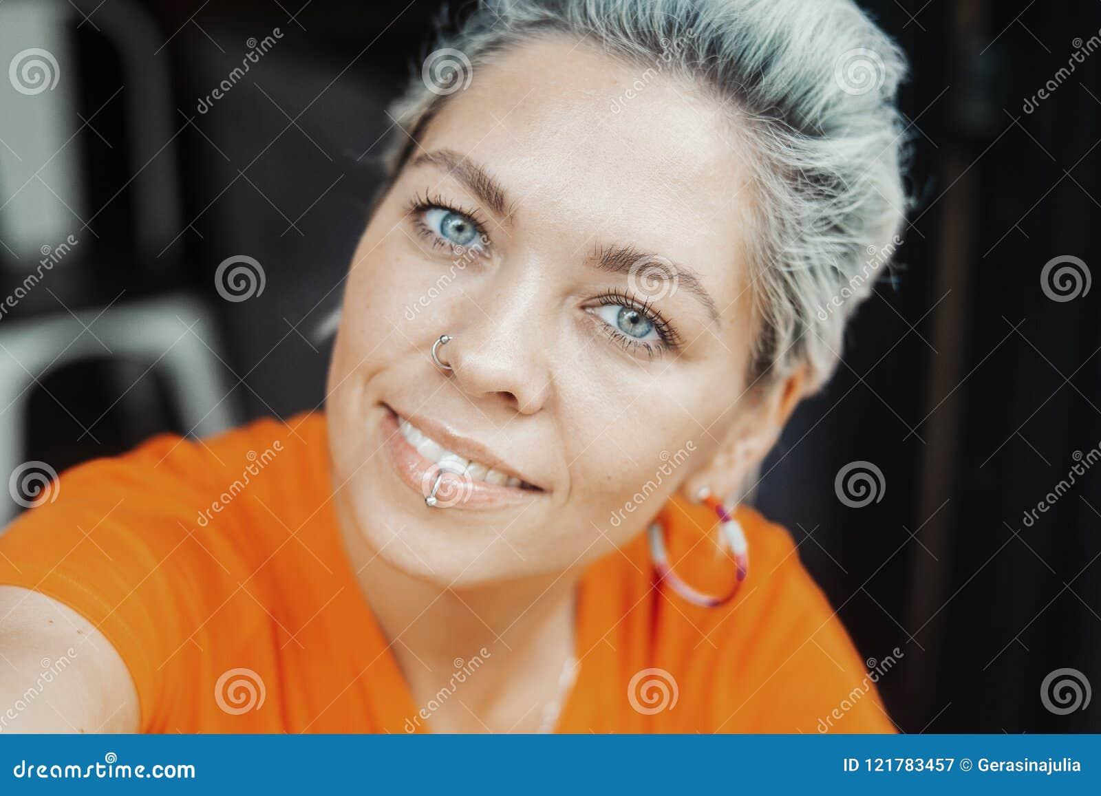 Attraktives blondes Mädchen im orange T-Shirt, das selfie am Café macht