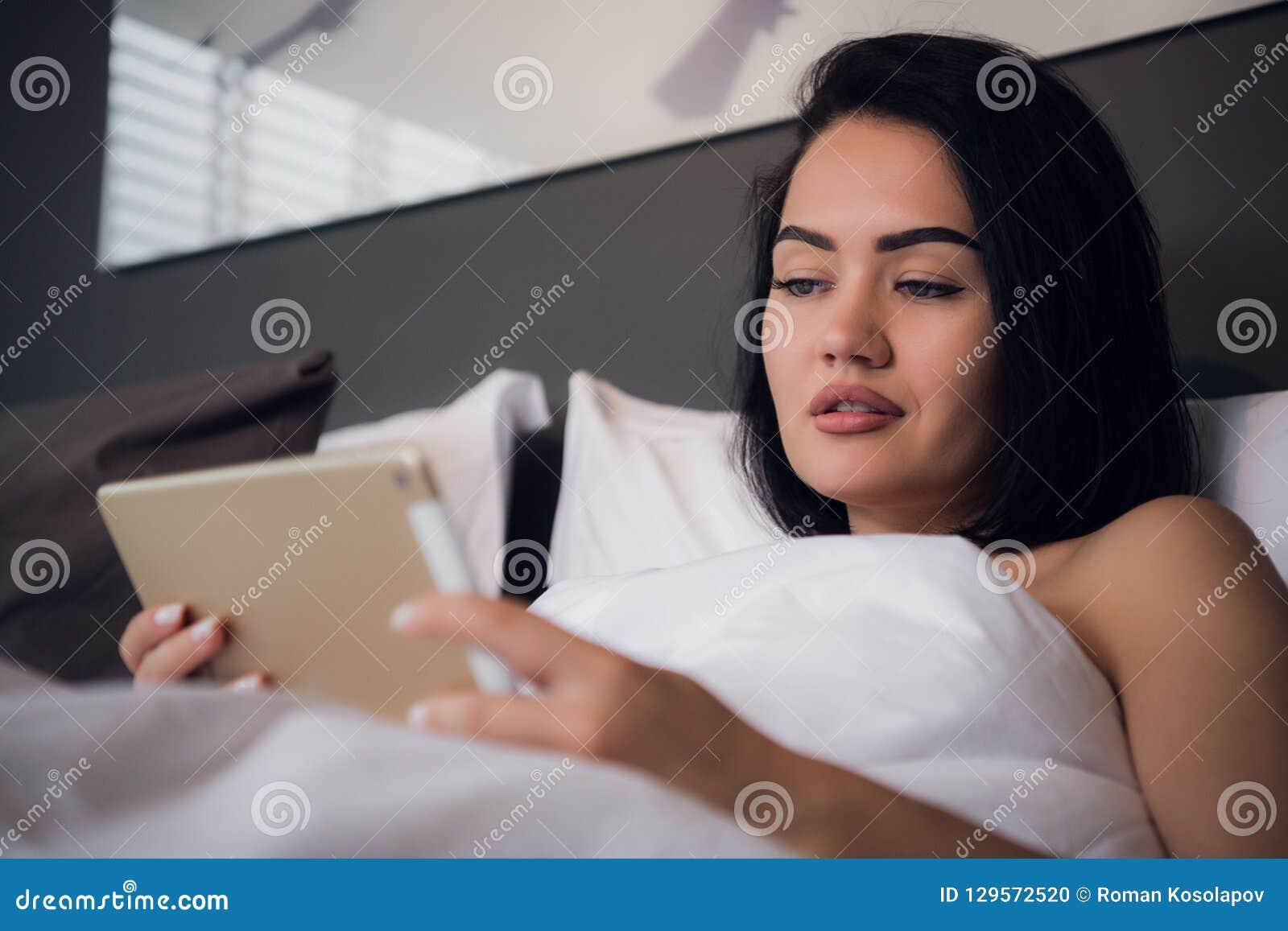Attraktives Brunettemädchen, das digitale Tablette mit leerem Bildschirm hält und im Schlafzimmer lächelt