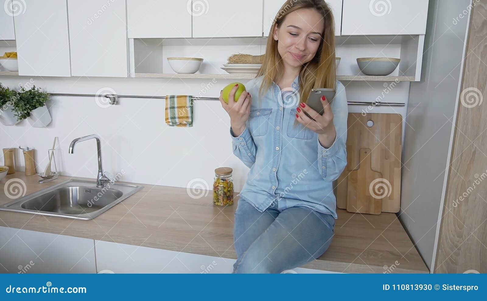 Attraktives Mädchen benutzt intelligentes Telefon und isst den Apfel und sitzt auf kitc