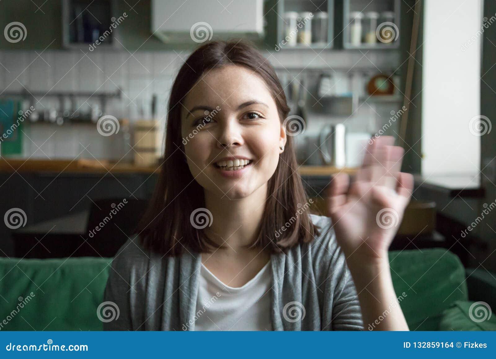 Attraktives Mädchen, das auf der Couch betrachtet Kamera sitzt
