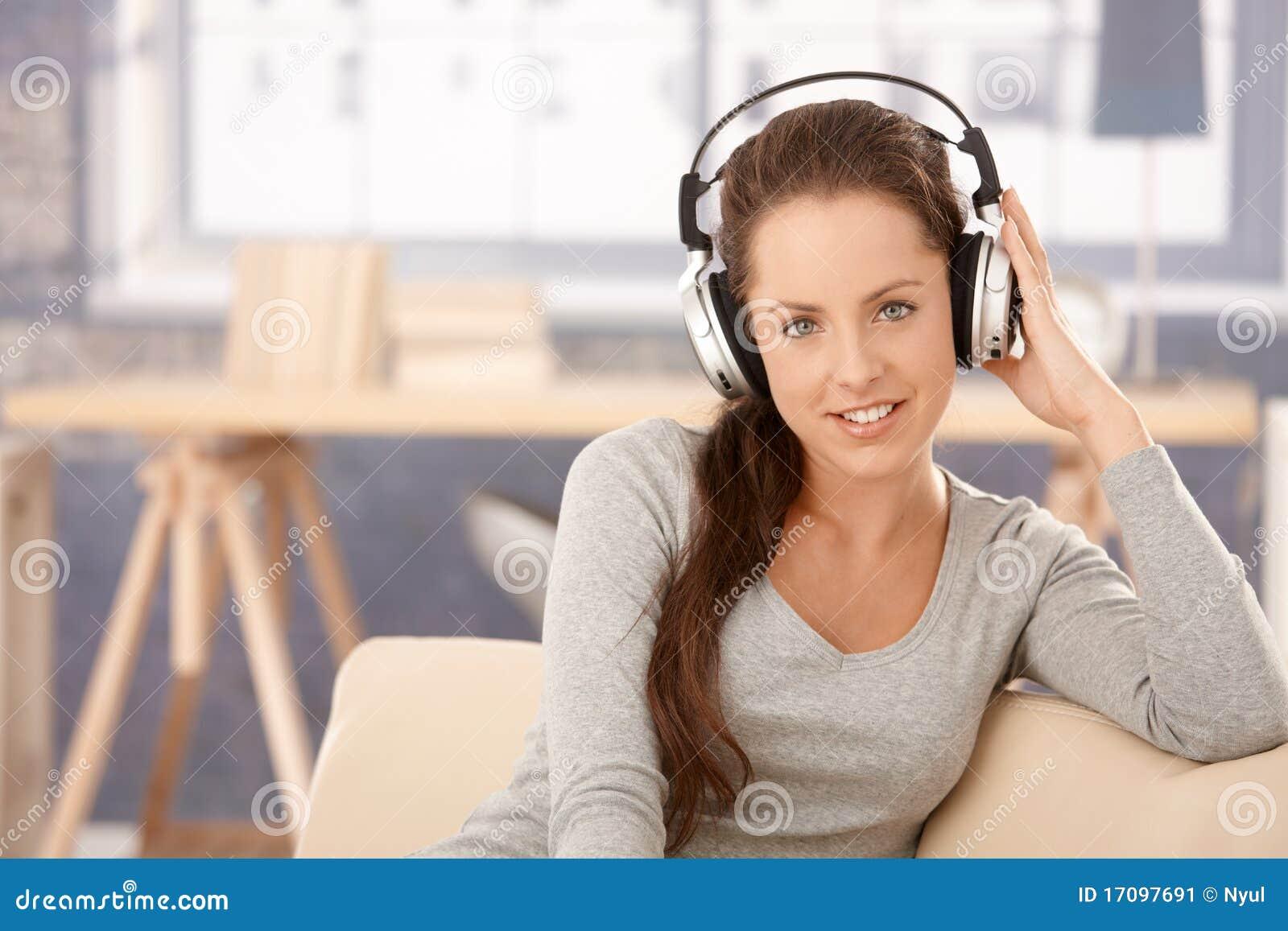 Attraktives Mädchen, das zu Hause lächelnde Musik hört