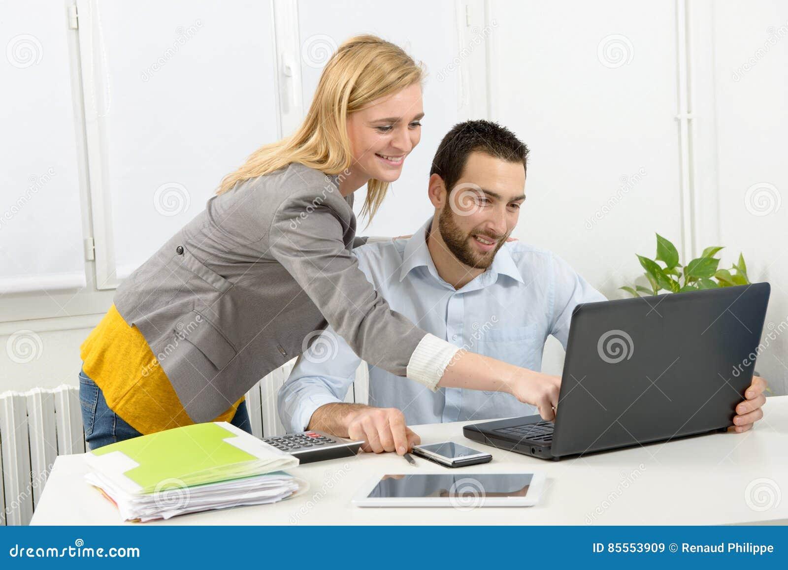 Attraktives Mann- und Frauengeschäft unter Verwendung der Laptop-Computers