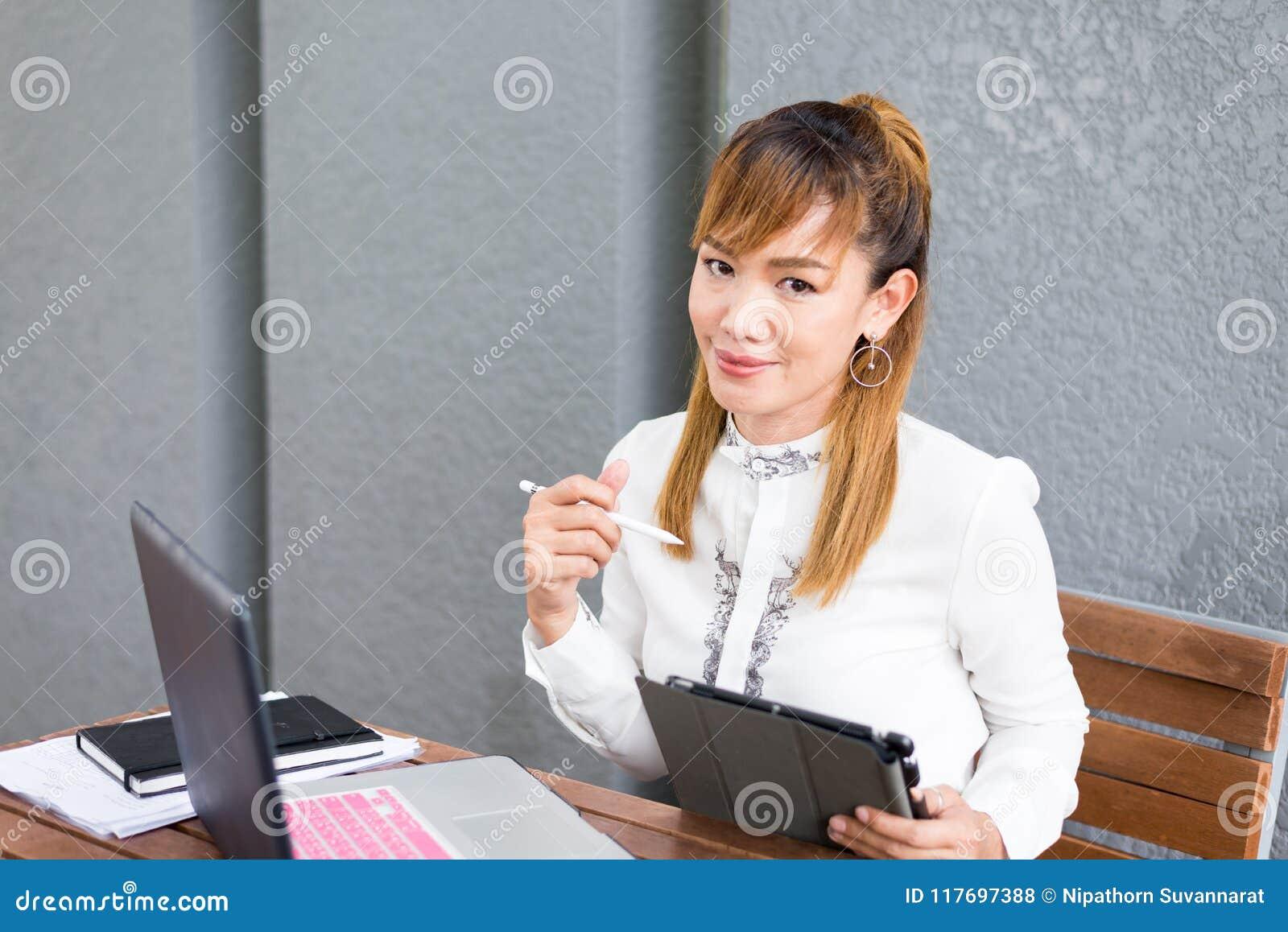 Attraktivt asiatiskt kinesiskt flickasammanträde parkerar på bänken som arbetar på den tillfälliga bärbar datorminnestavlan