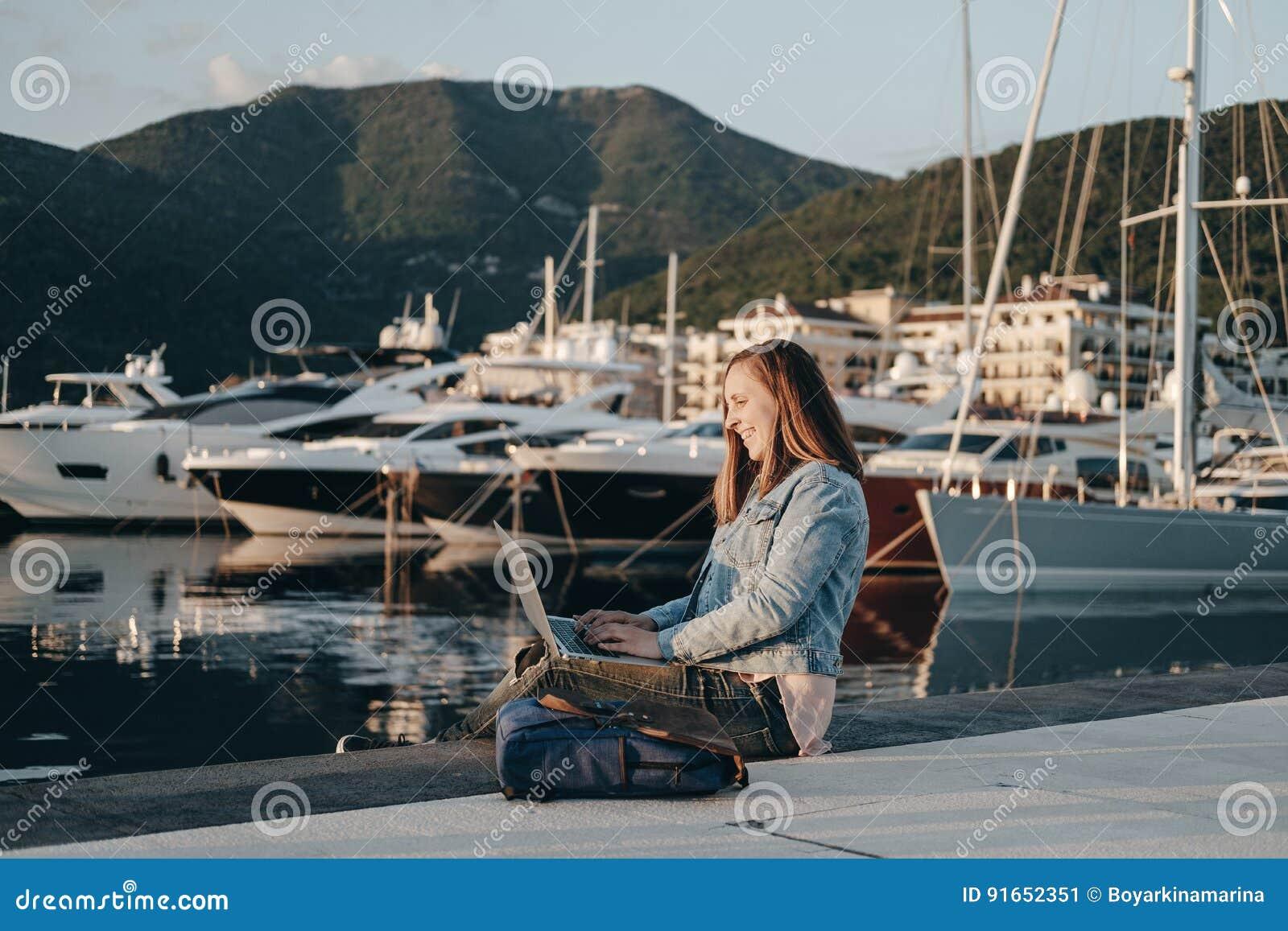 Attraktivt sammanträde för ung kvinna på invallning på stranden på solen