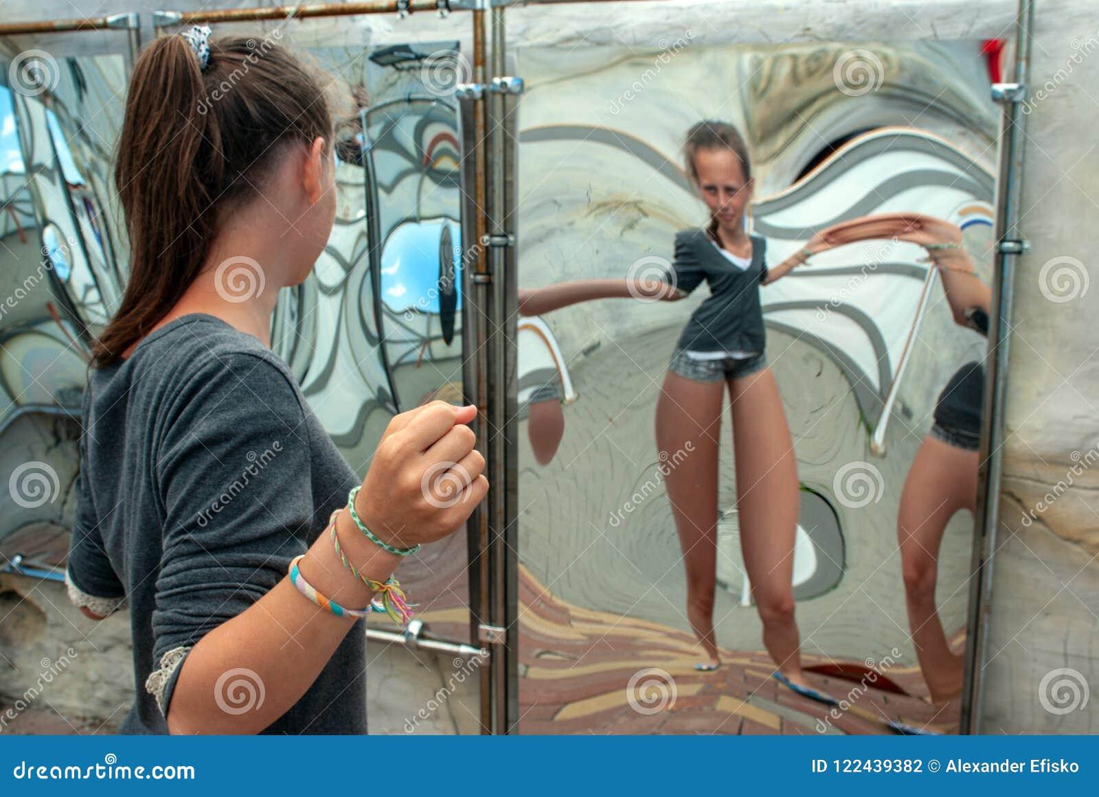 Attrazione, ragazza che esamina la sua immagine nello specchio distorto nel corridoio degli specchi