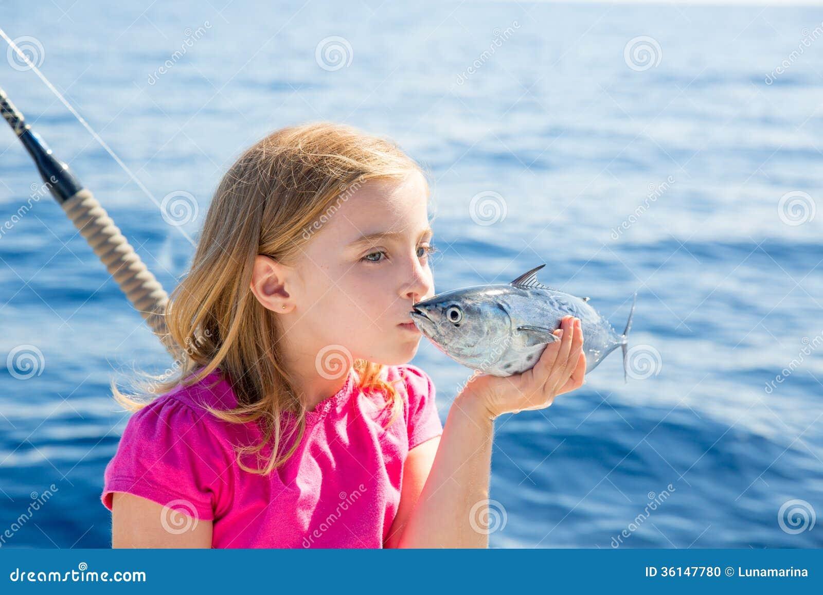 Atuns pequenos do atum louro da pesca da menina da criança que beijam para a liberação
