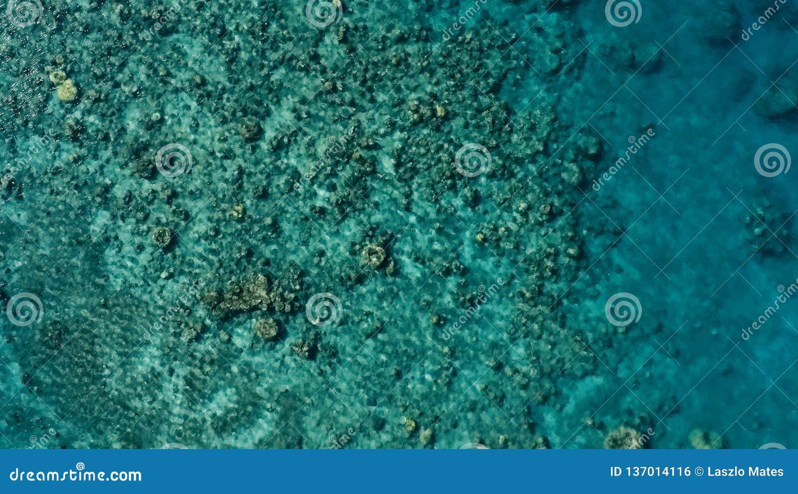 Aturdindo a imagem aérea do zangão do um barco de pesca pequeno que incorpora uma ancoragem do oceano do mar da a um canal ao lad