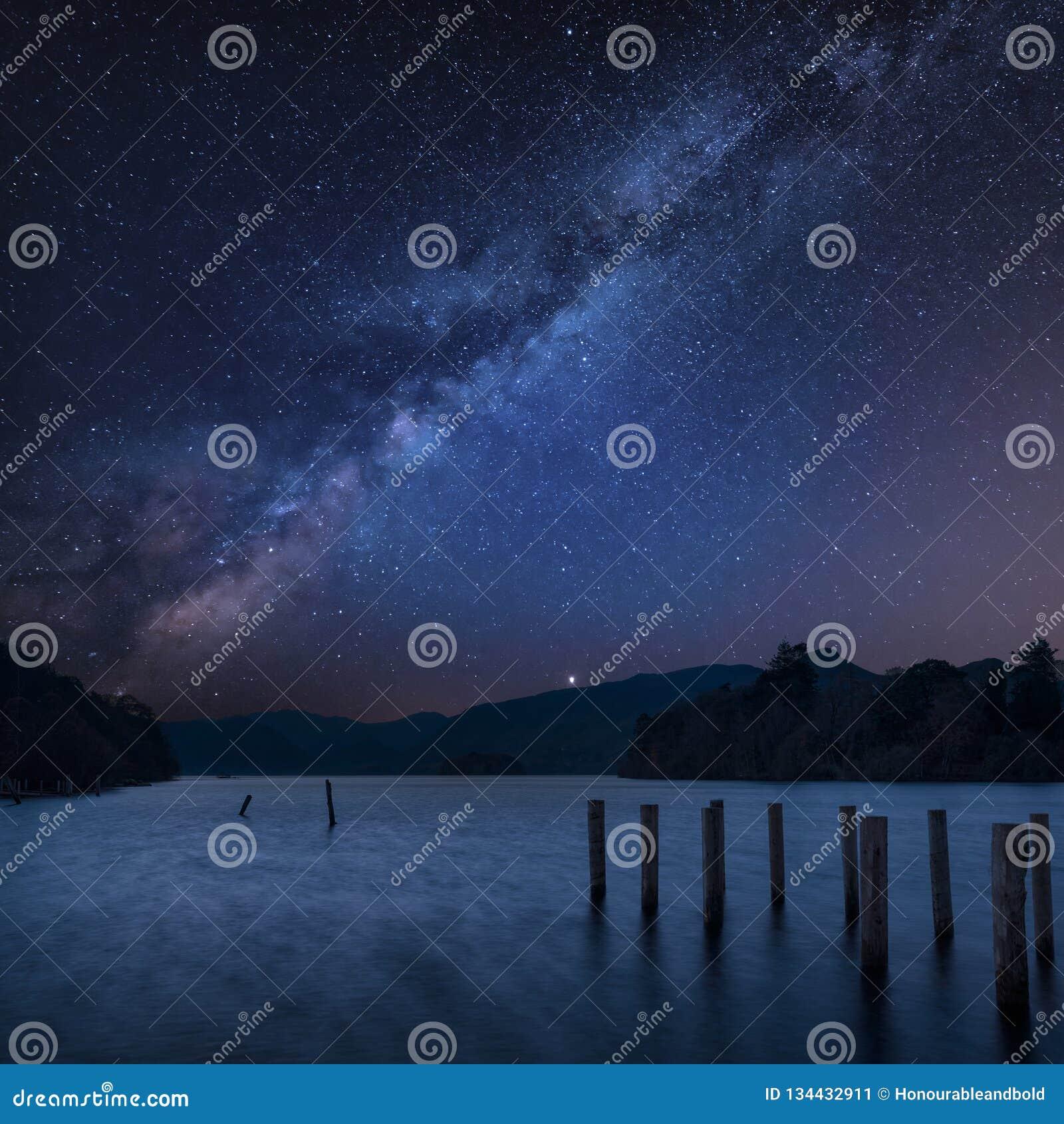 Aturdindo a imagem composta da paisagem da Via Látea vibrante sobre a água de Derwent no distrito do lago durante o nascer do sol