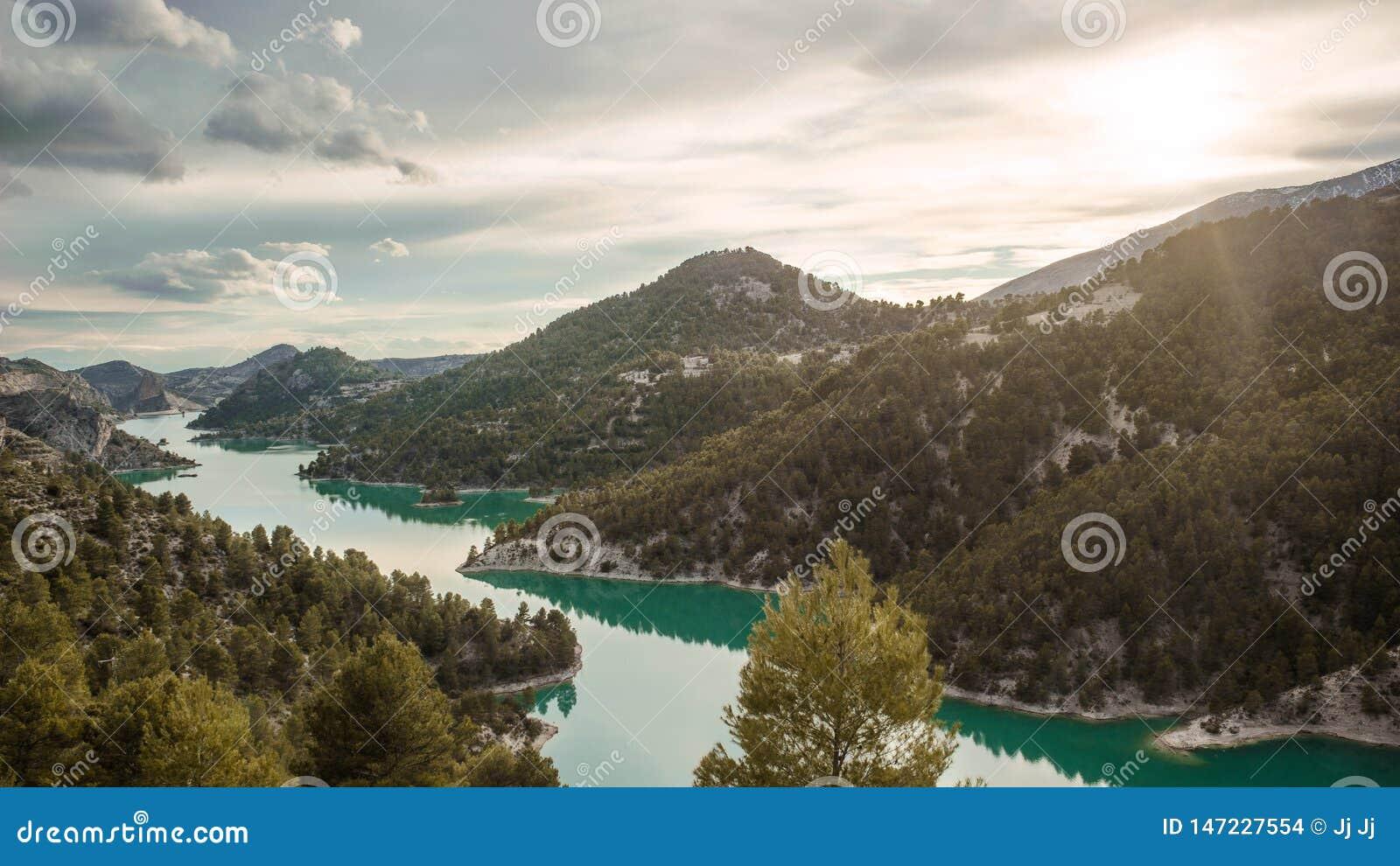 Aturdindo a vista do EL Portillo do lago com o sol que shinning acima das montanhas Terra da fantasia