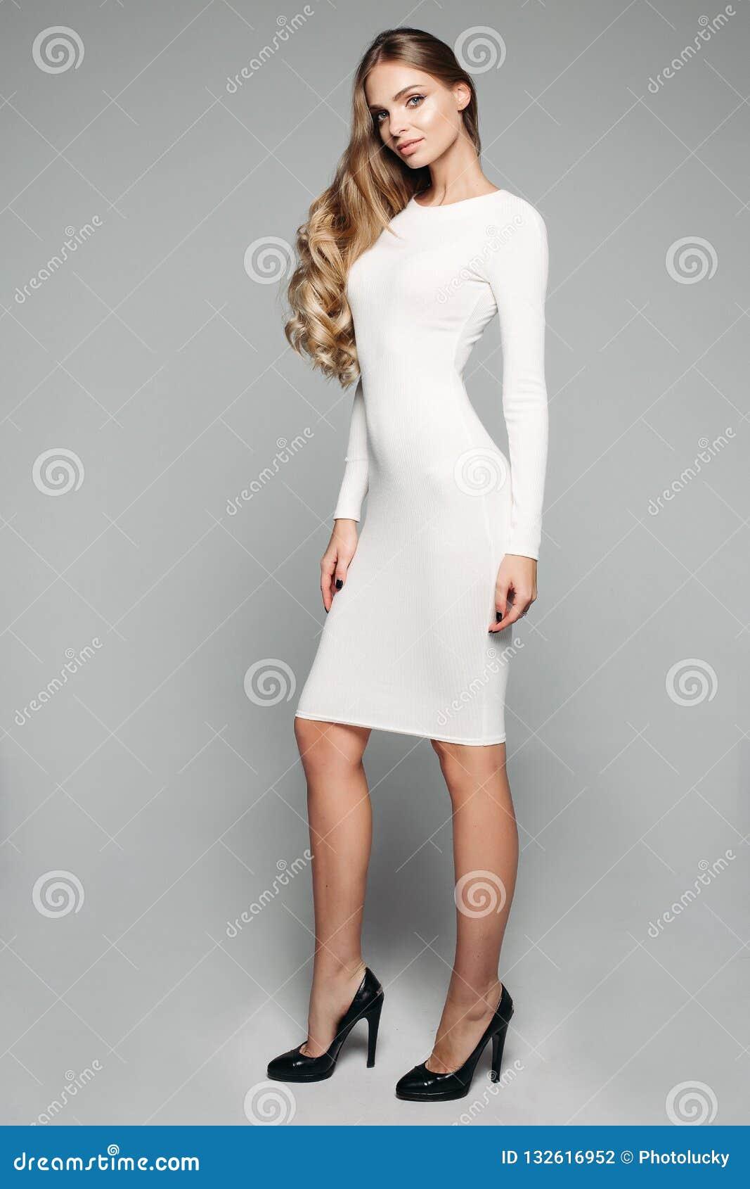 89bb60e8b Aturdir a la muchacha rubia en el vestido simple blanco y talones negros