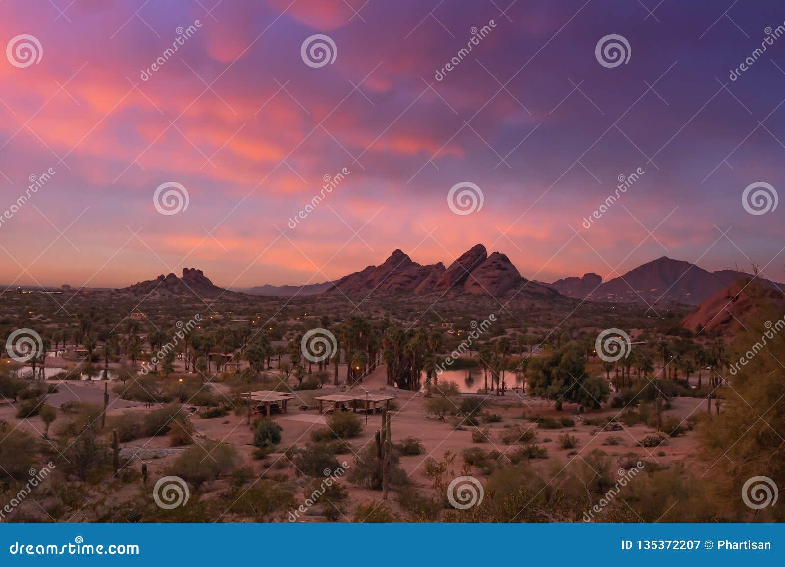 Aturdir puesta del sol sobre Phoenix, Arizona, parque de Papago en primero plano