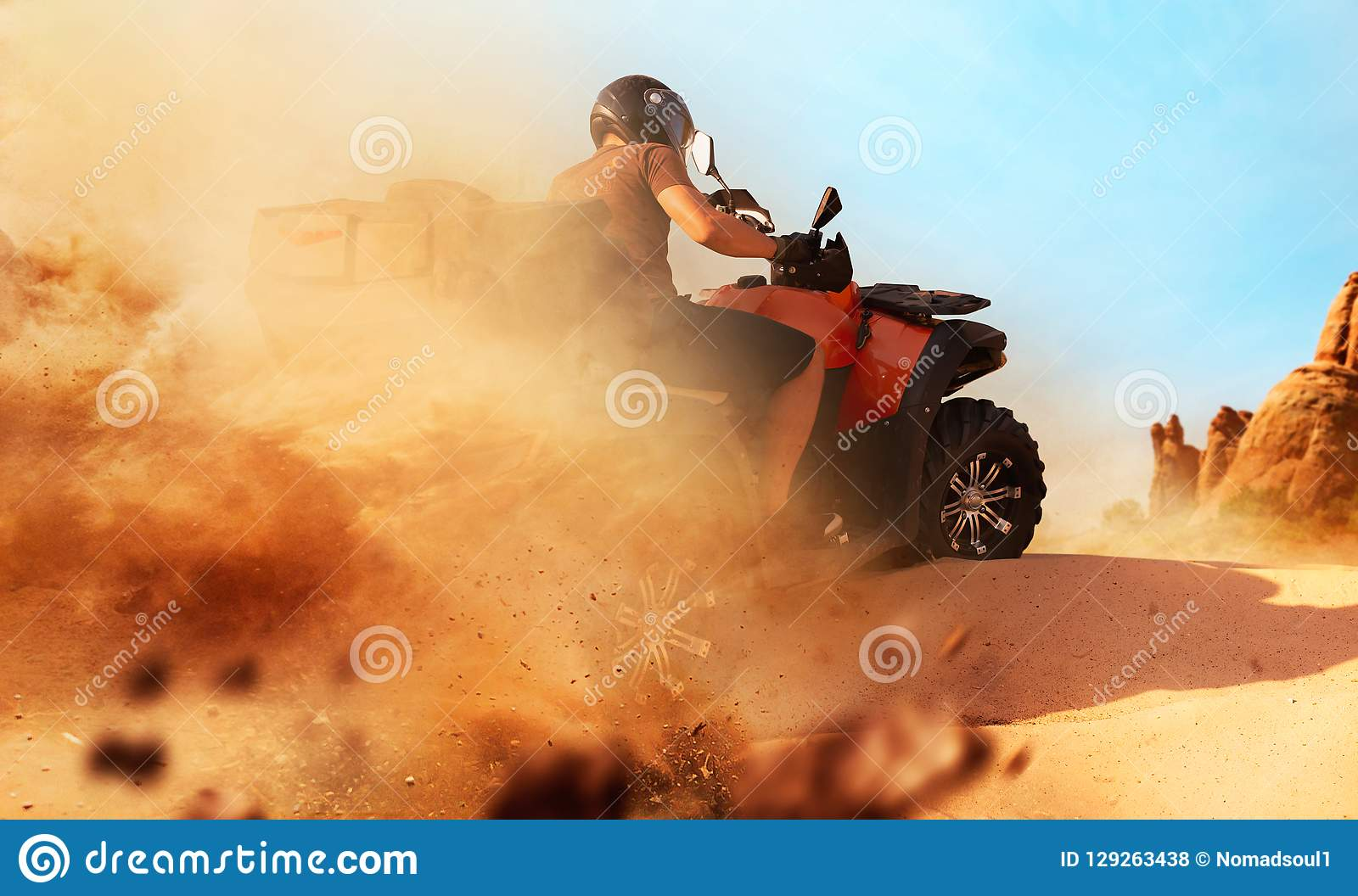 Atv riding in sand quarry, dust clouds, quad bike