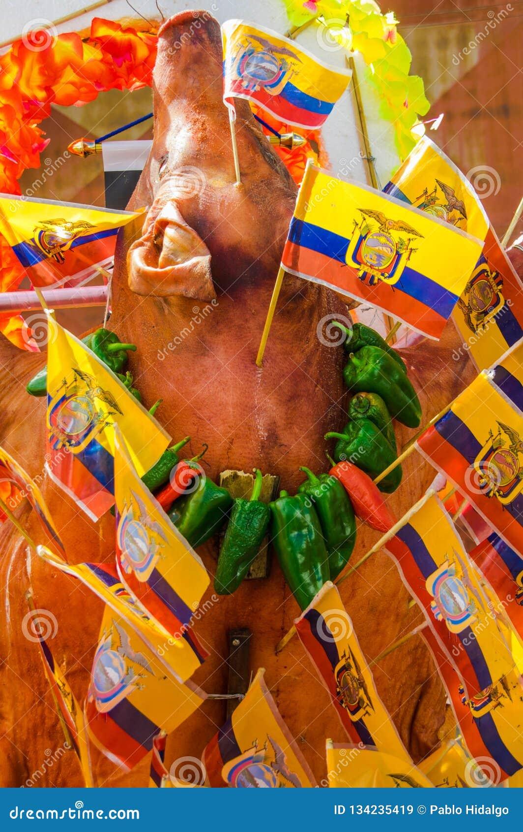 Au-dessus de la vue du corps de porc de roaste avec les drapeaux ecuadorian autour du corps et les poivrons magnifiques autour du