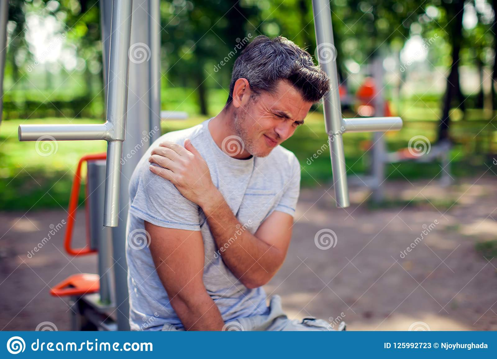 A man feeling pain in his shoulder during sport and workout in t