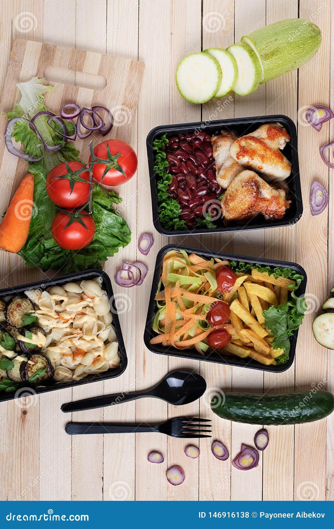 Aubergines frites dans le conteneur avec les ailes et les l?gumes crus de poulet grill?s sur le fond rustique, la tomate-cerise e