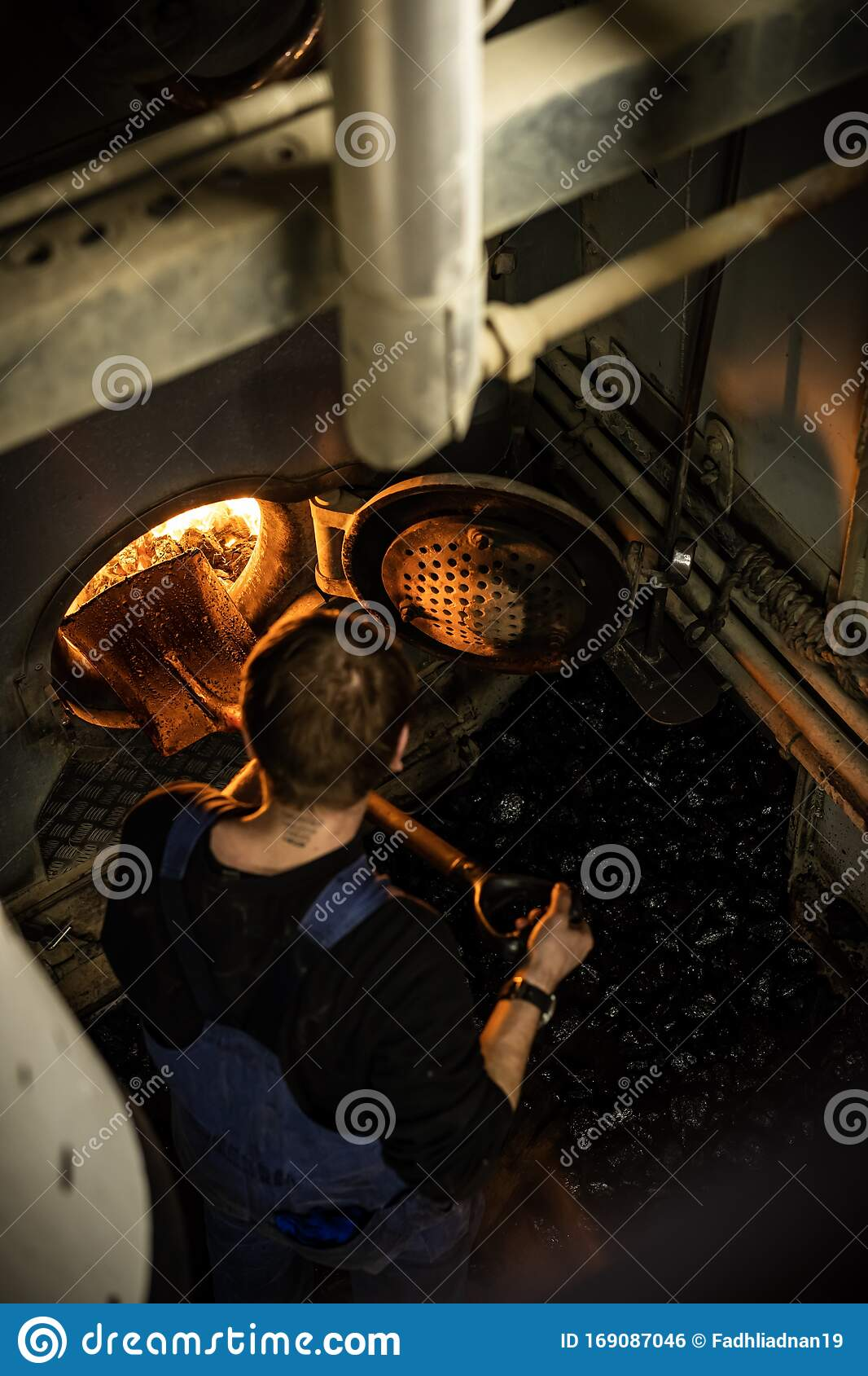 Steam Ship Engine Room: A Worker Insert A Coal Inside The Engine Of Coaled Power