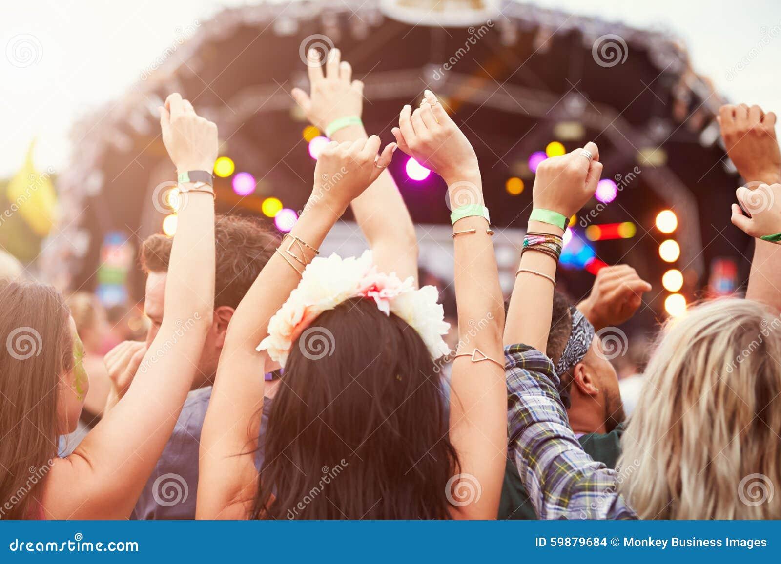 Audiência com mãos no ar em um festival de música