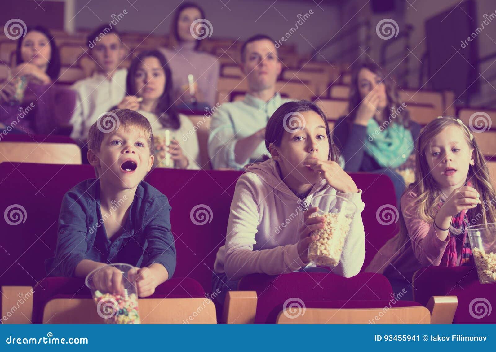 Audiência entusiástica que atende à noite de cinema com pipoca