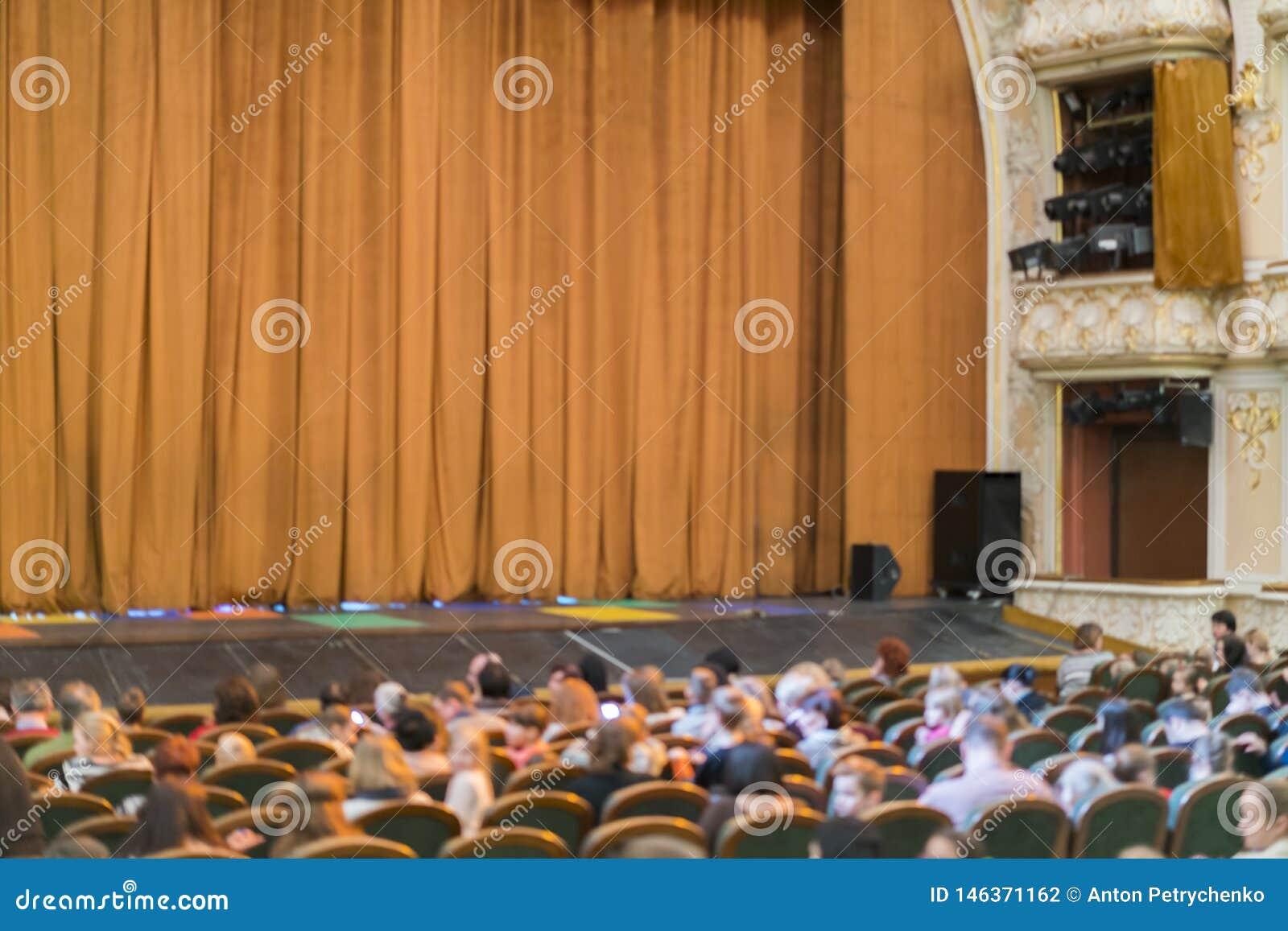 Audi?ncia no teatro cortina fechado da fase em um teatro blurry