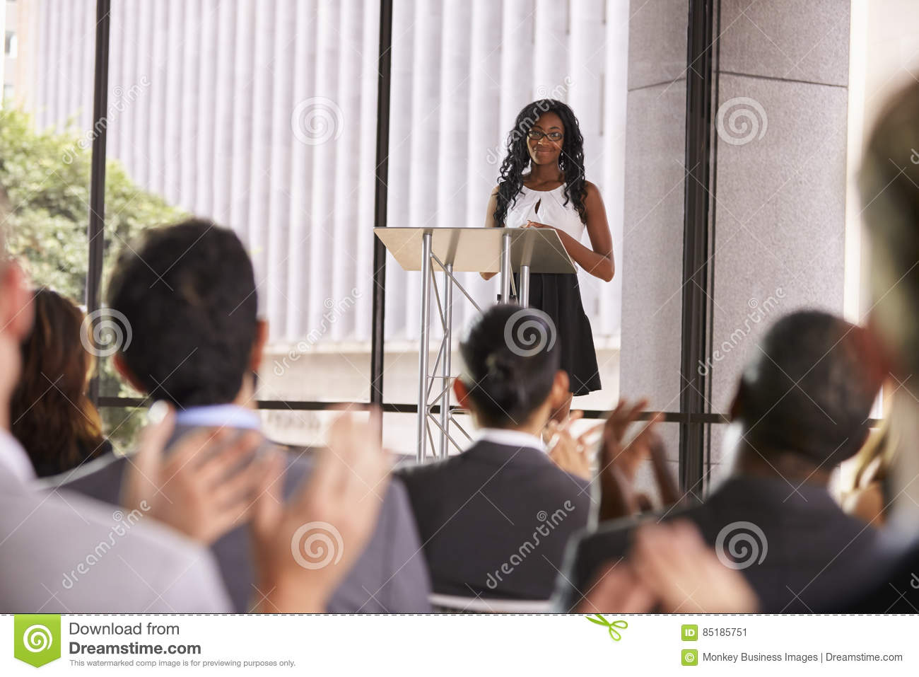 Audience at seminar applauding young black woman at lectern