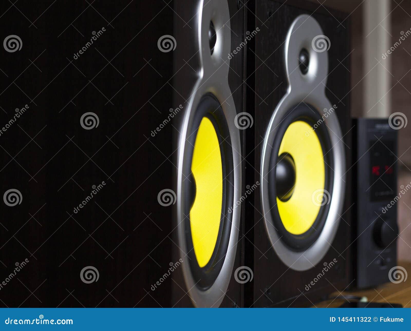 Audio sistema che gioca via gli altoparlanti gialli mobili e grandi collegati al telefono