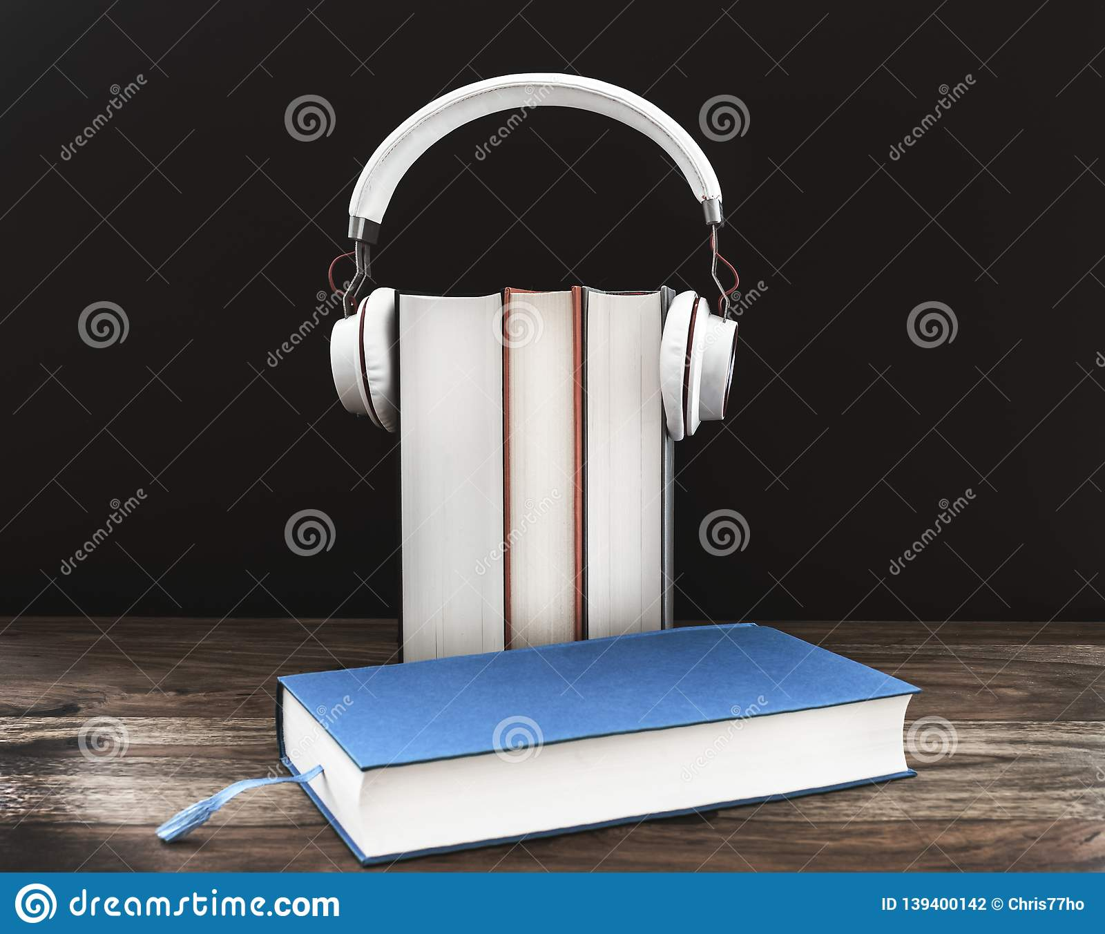 Audiobook concept with headphones on hardcover books against dark background