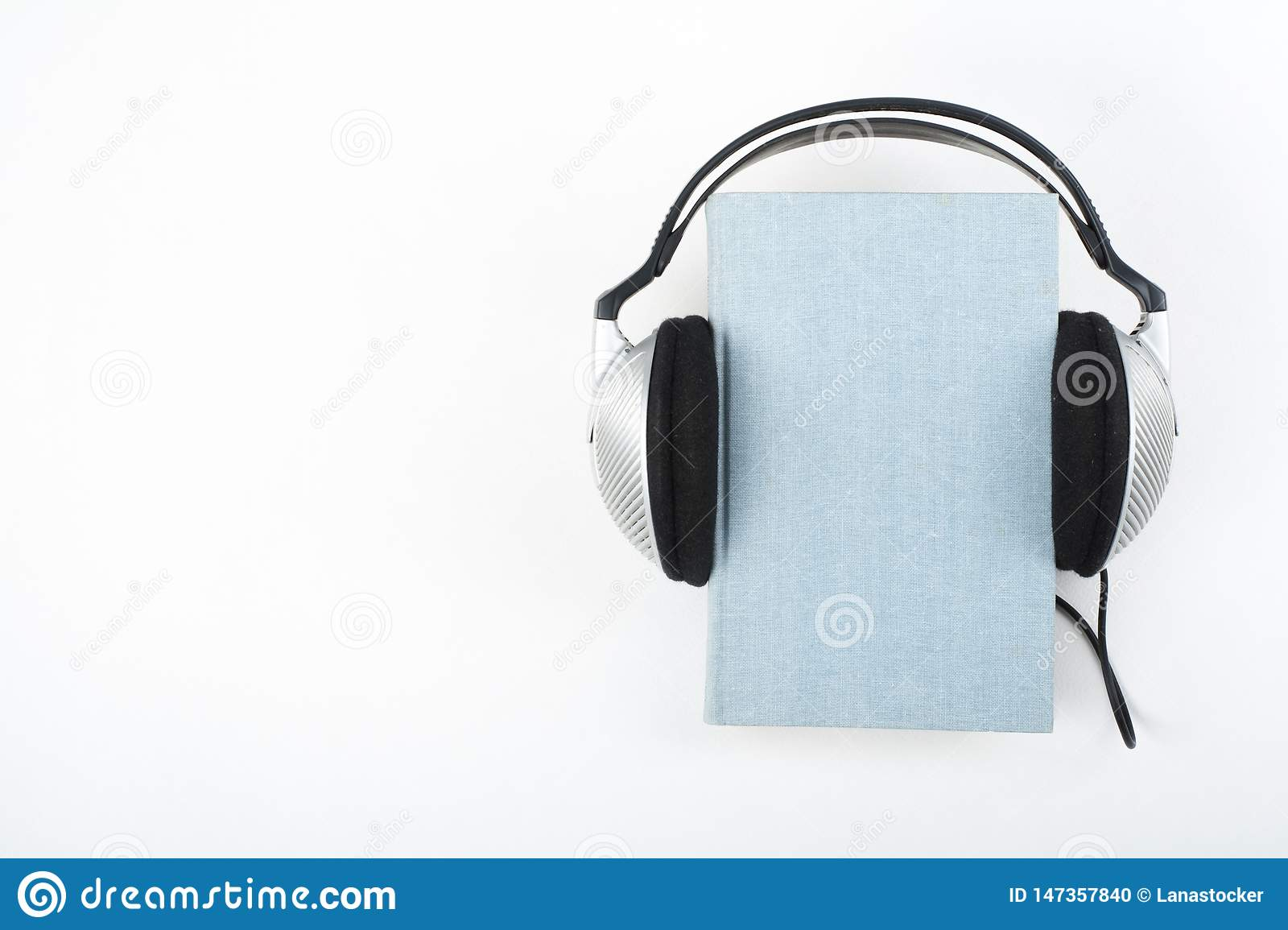 Audiobook on white background. Headphones put over blue hardback book, empty cover, copy space for ad text. Distance