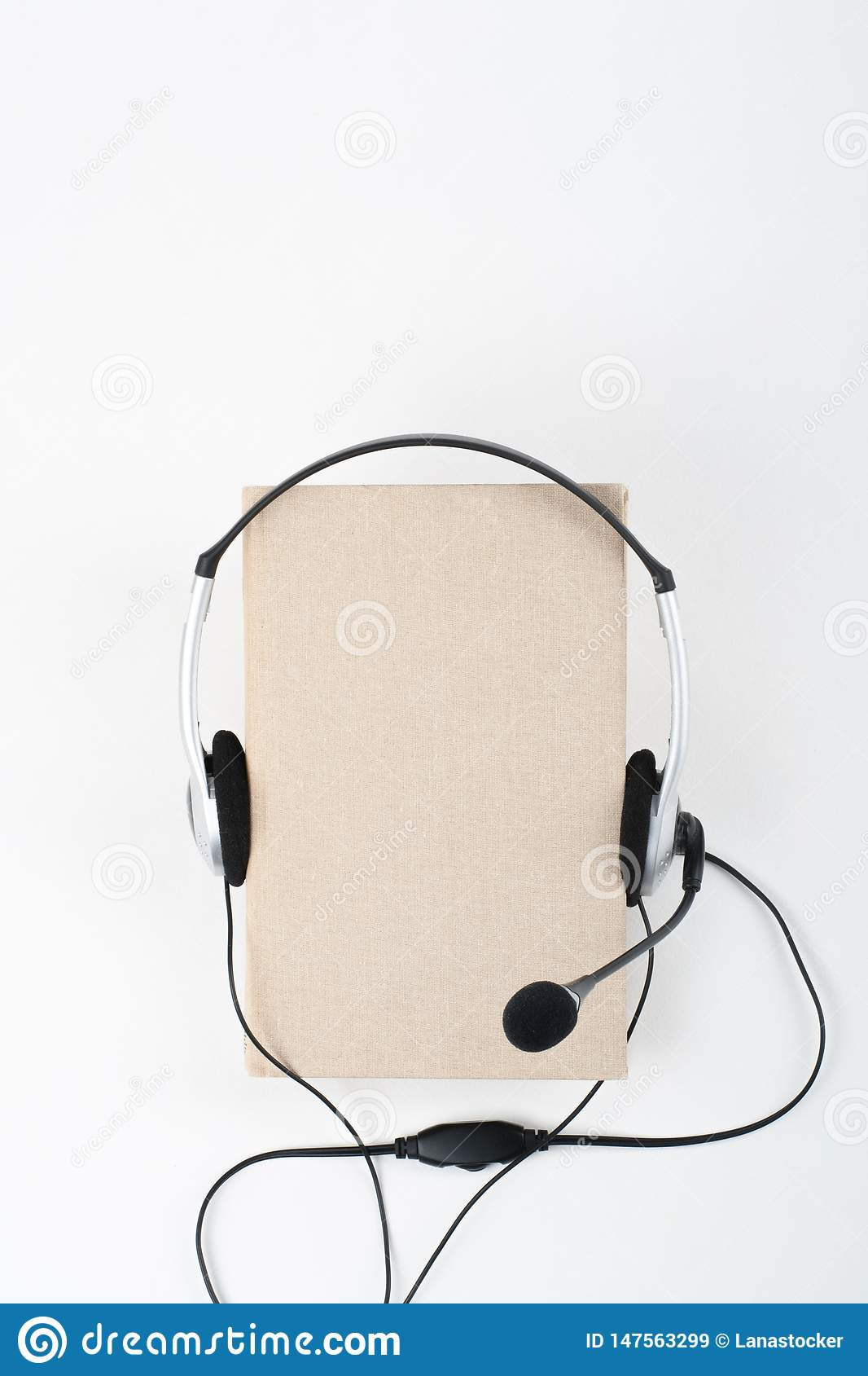 Audiobook on white background. Headphones put over yellow hardback book, empty cover, copy space for ad text. Distance