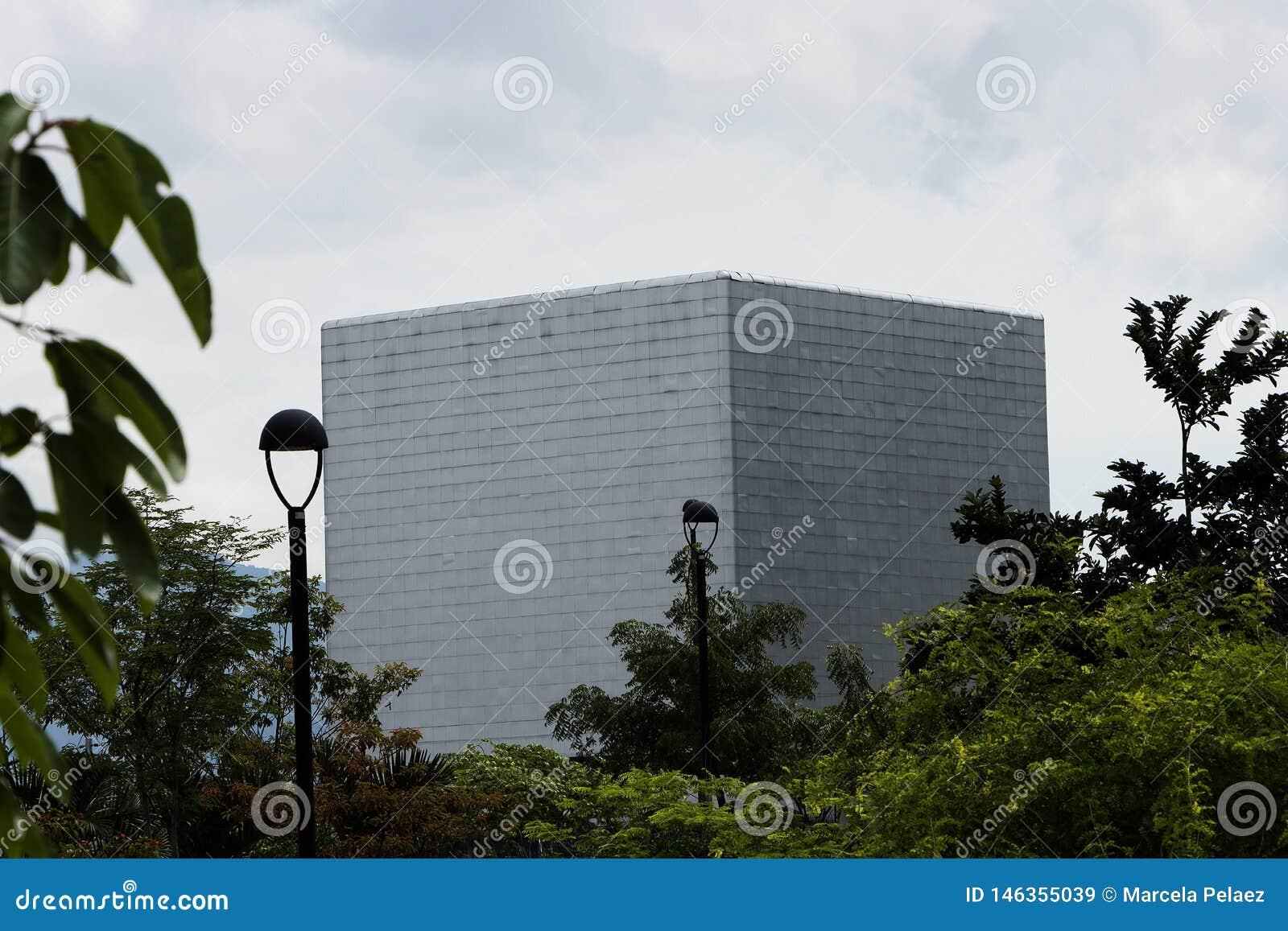 Auditório em Medellin na forma do cubo ao lado das empresas públicas que constroem com céu branco