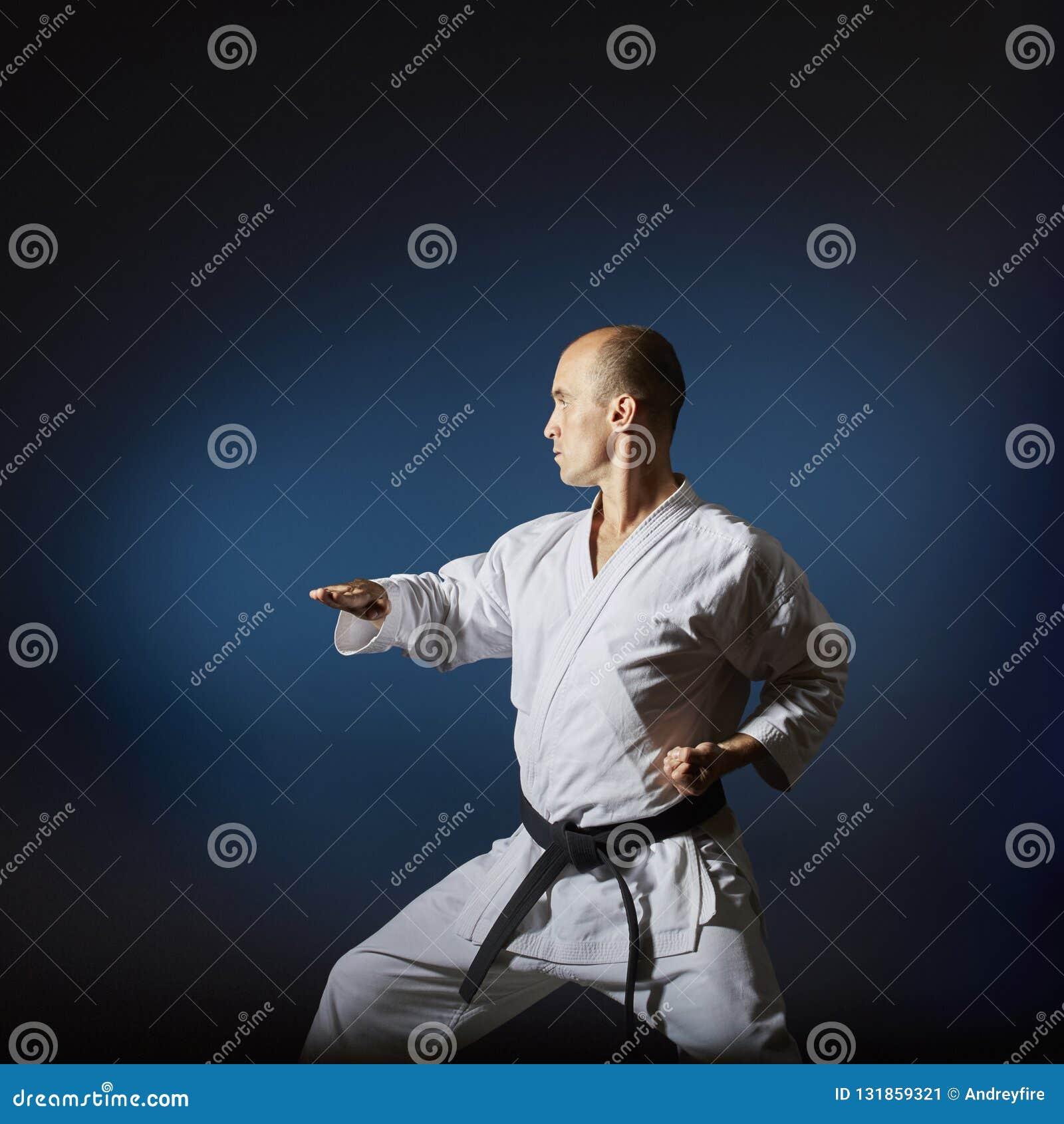 Auf einem blauen Hintergrund mit einer Steigung, bildet ein Athlet mit einem schwarzen Gürtel formal Karateübungen aus