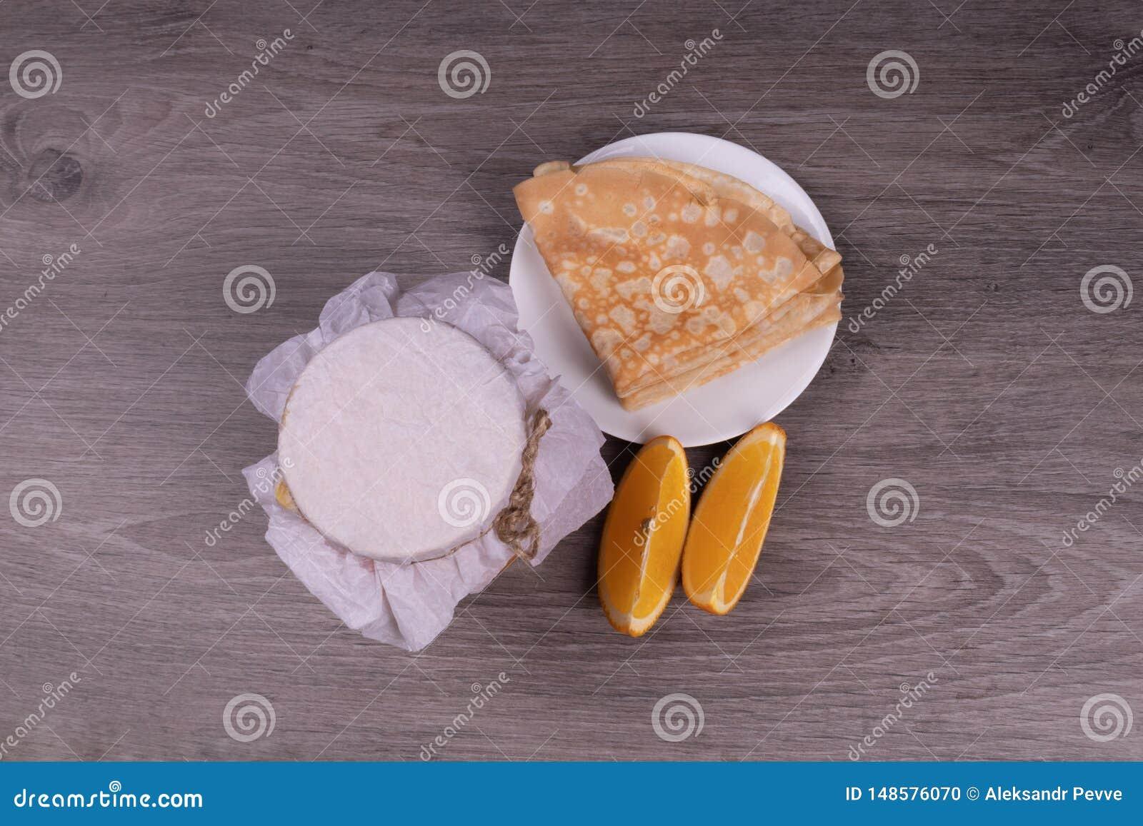 Auf einem h?lzernen Hintergrund eine Platte mit Pfannkuchen, ein Glas unter einem Papierdeckel einer Zitronenkeilansicht von der