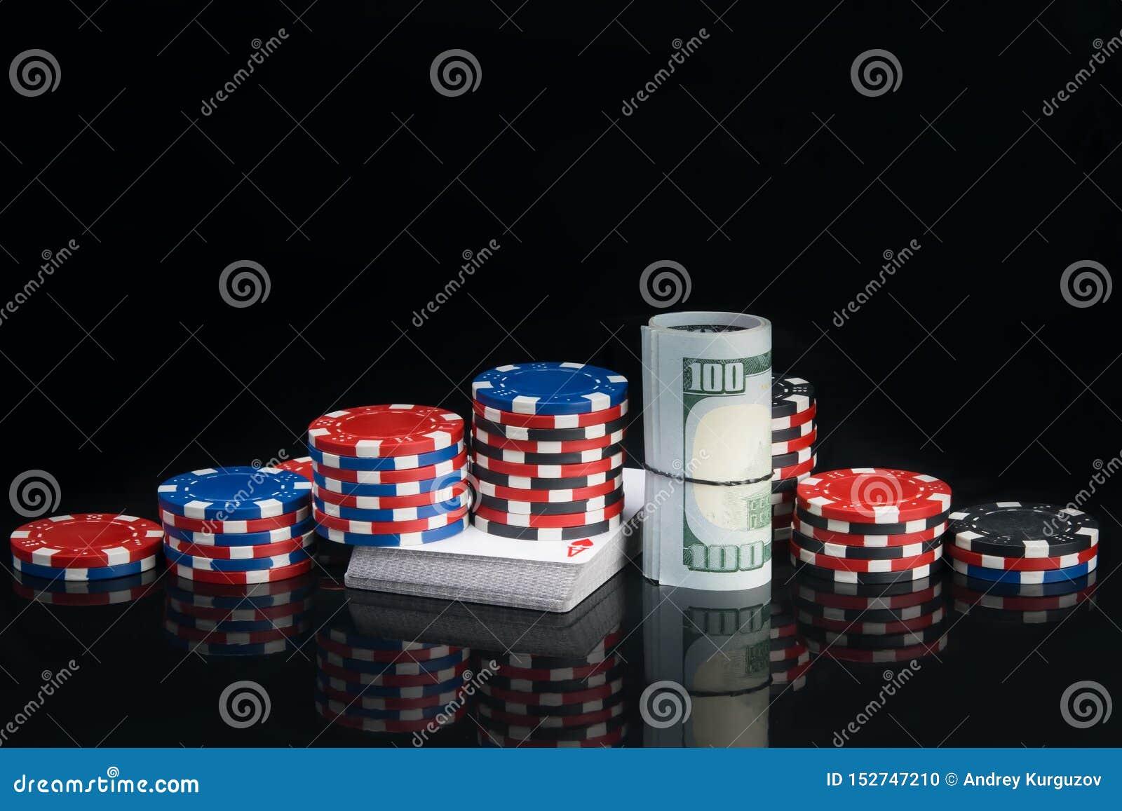 Auf einem schwarzen Hintergrund mit einer Reflexion, rollten eine Pyramide von Pokerchips und hundert Dollarscheine oben auf eine