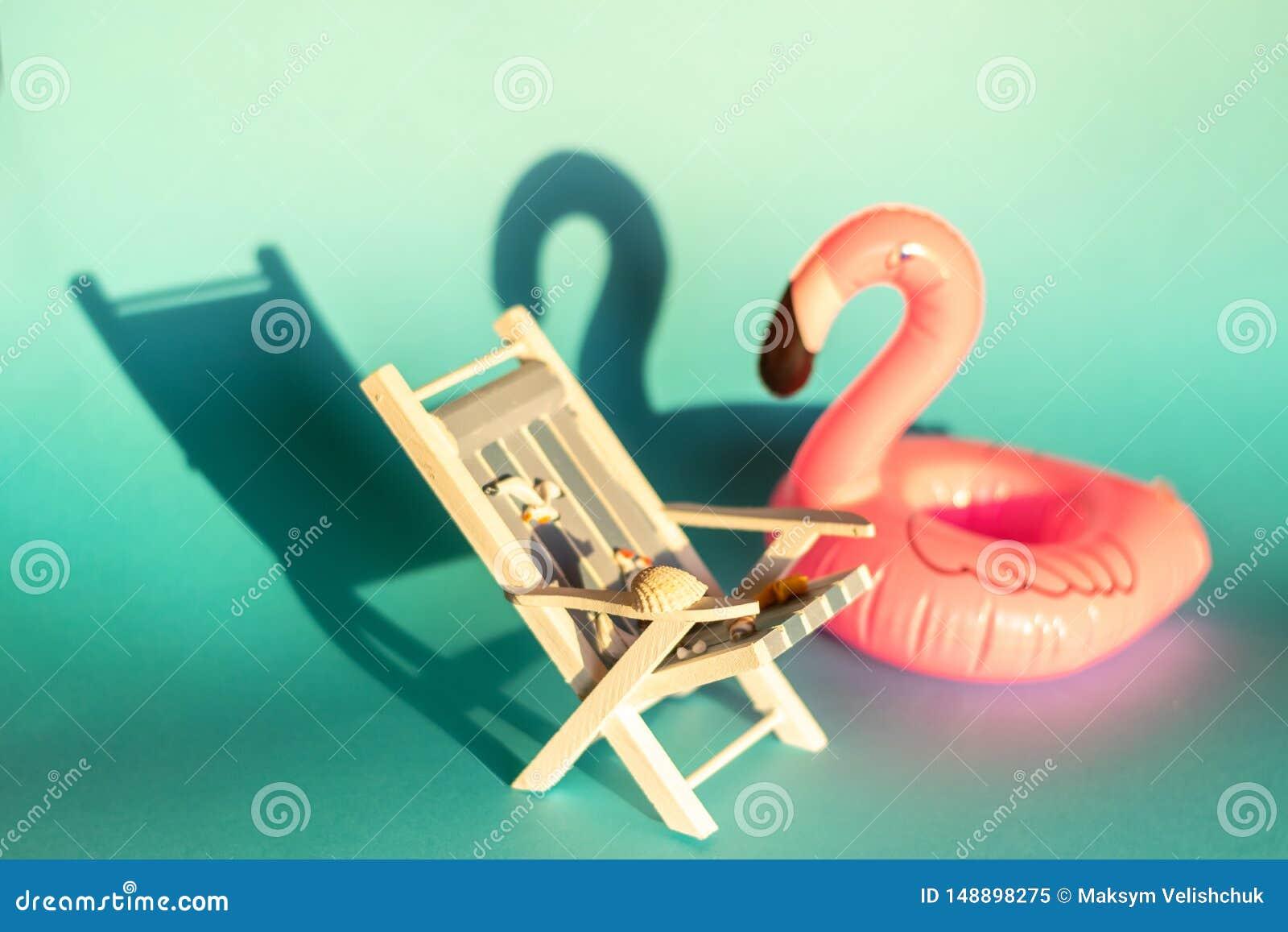 Aufblasbarer Flamingo und deckchair auf einem blauen Hintergrund, Poolflosspartei,