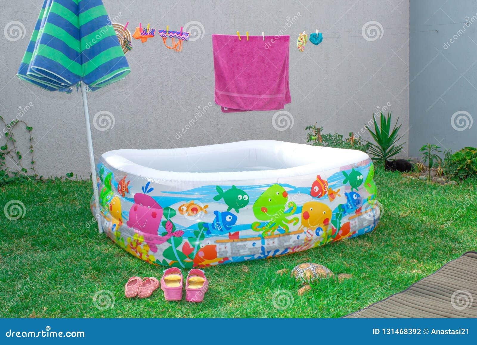 Aufblasbares Pool im Garten, mit einem Regenschirm