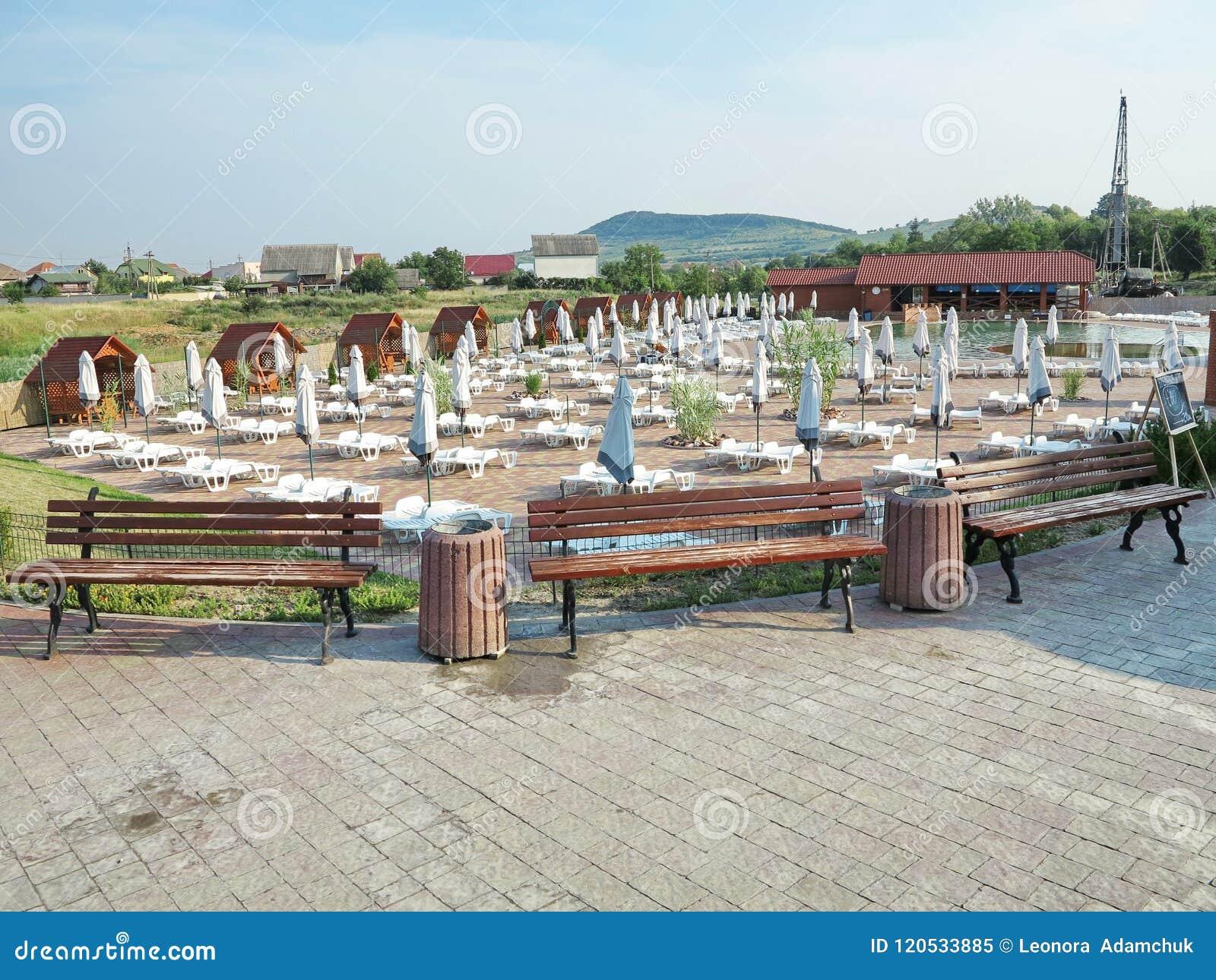 Aufenthaltsräume für Entspannung und Regenschirme bauten auf dem Poolbereich zusammen
