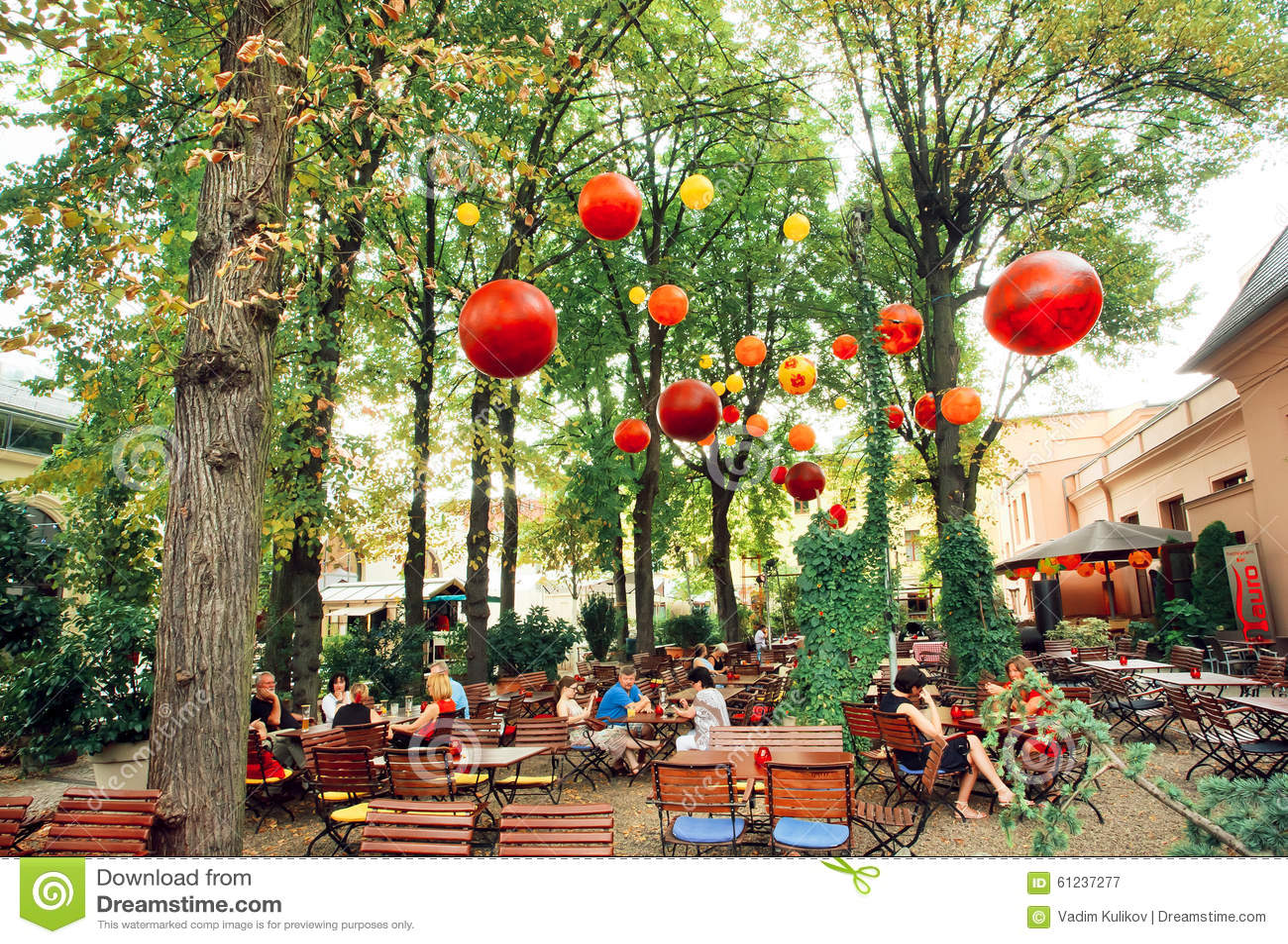 Aufenthaltsraumrestaurant mit den Leuten, die unter grünen Bäumen sich entspannen