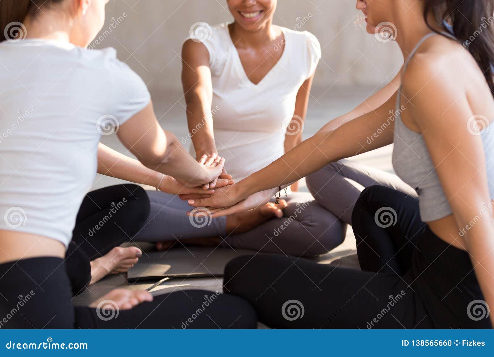 Aufgeregte geeignete Frauen schließen sich den Händen an, die Einheit am Training zeigen