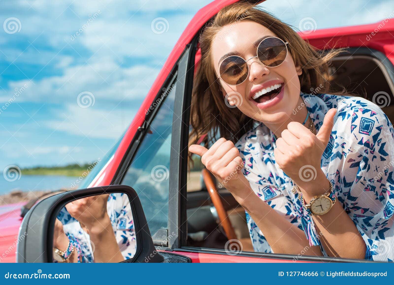 Aufgeregte junge Frau in der Sonnenbrille, die im Auto sitzt und sich Daumen zeigt