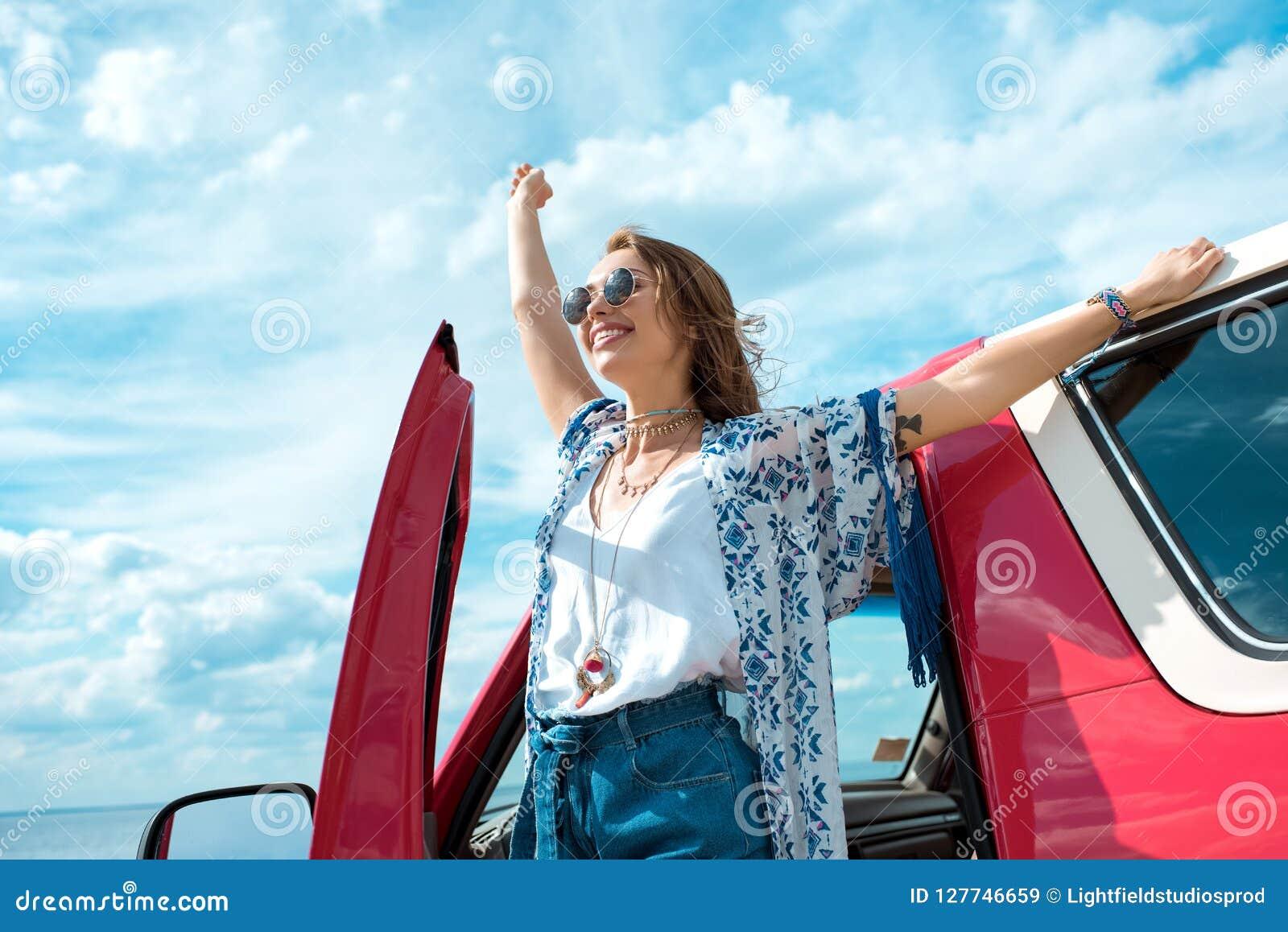 Aufgeregte junge Frau in der Sonnenbrille, die nahe Auto steht