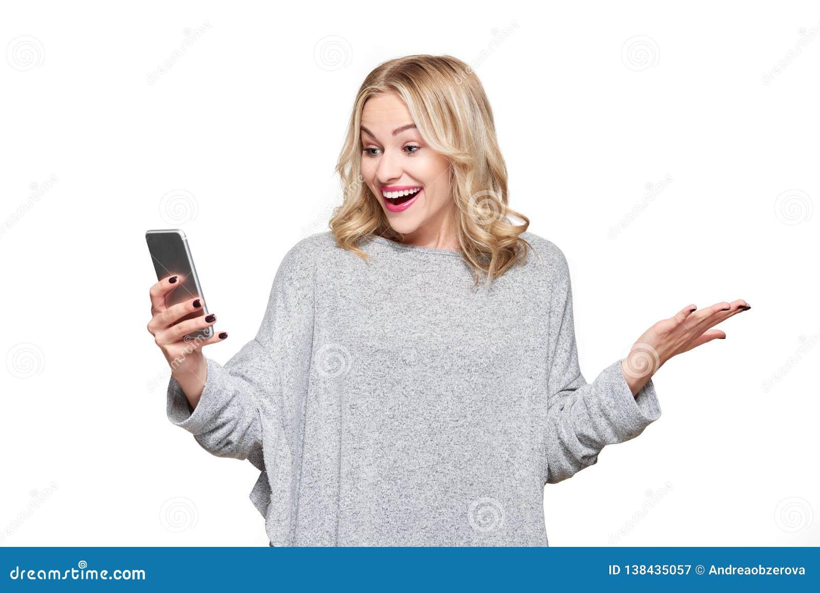 Aufgeregte junge Frau, die ihren Handy im Unglauben lächelt und feiert betrachtet Frauenlesepositive Textnachricht