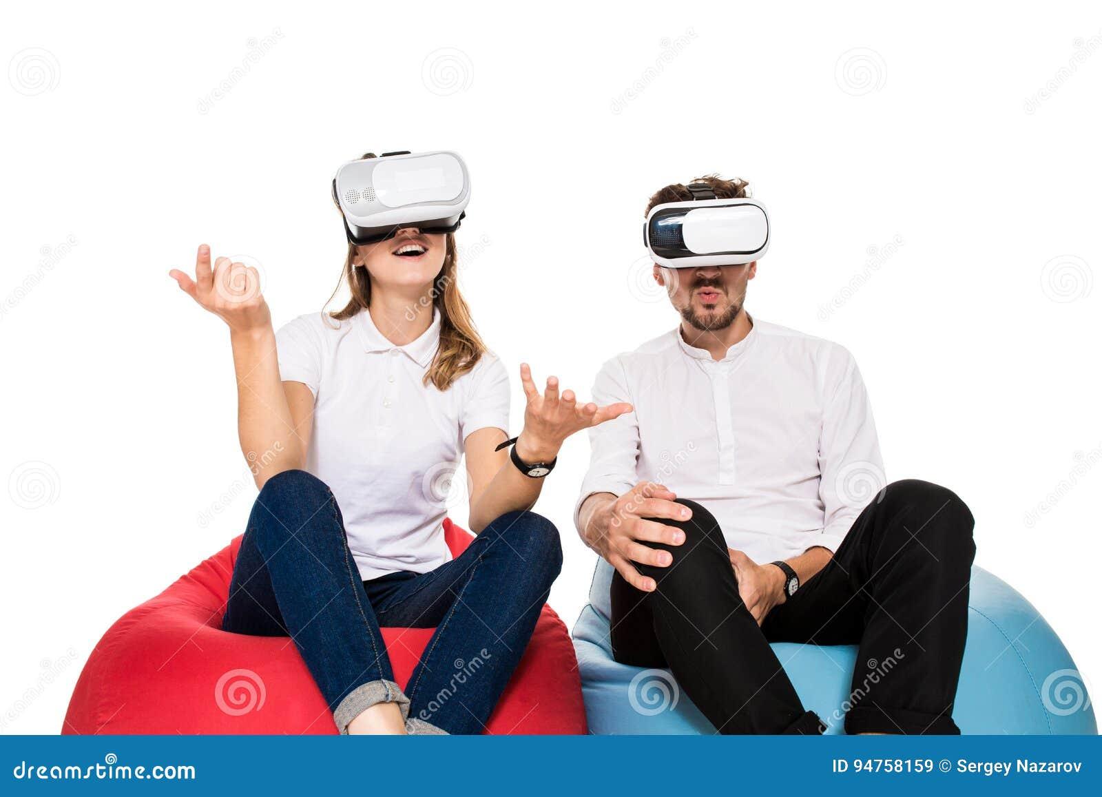 Aufgeregte junge Paare, welche die virtuelle Realität gesetzt auf den Sitzsäcken lokalisiert auf weißem Hintergrund erfahren
