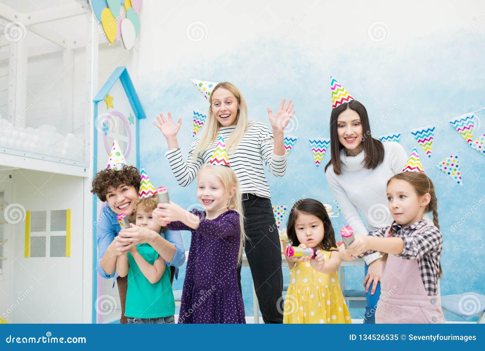 Aufgeregte Mütter, die Spaß mit Kindern an der Geburtstagsfeier haben