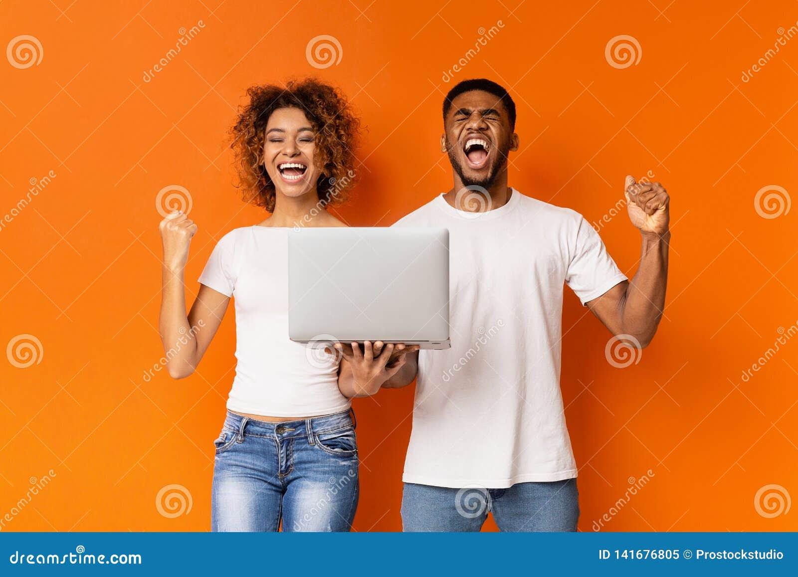 Aufgeregte schwarze Paare, die Gewinn mit Laptop feiern