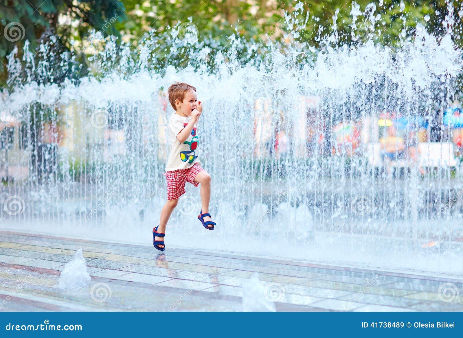 Aufgeregter Junge, der zwischen Wasserstrom im Stadtpark läuft