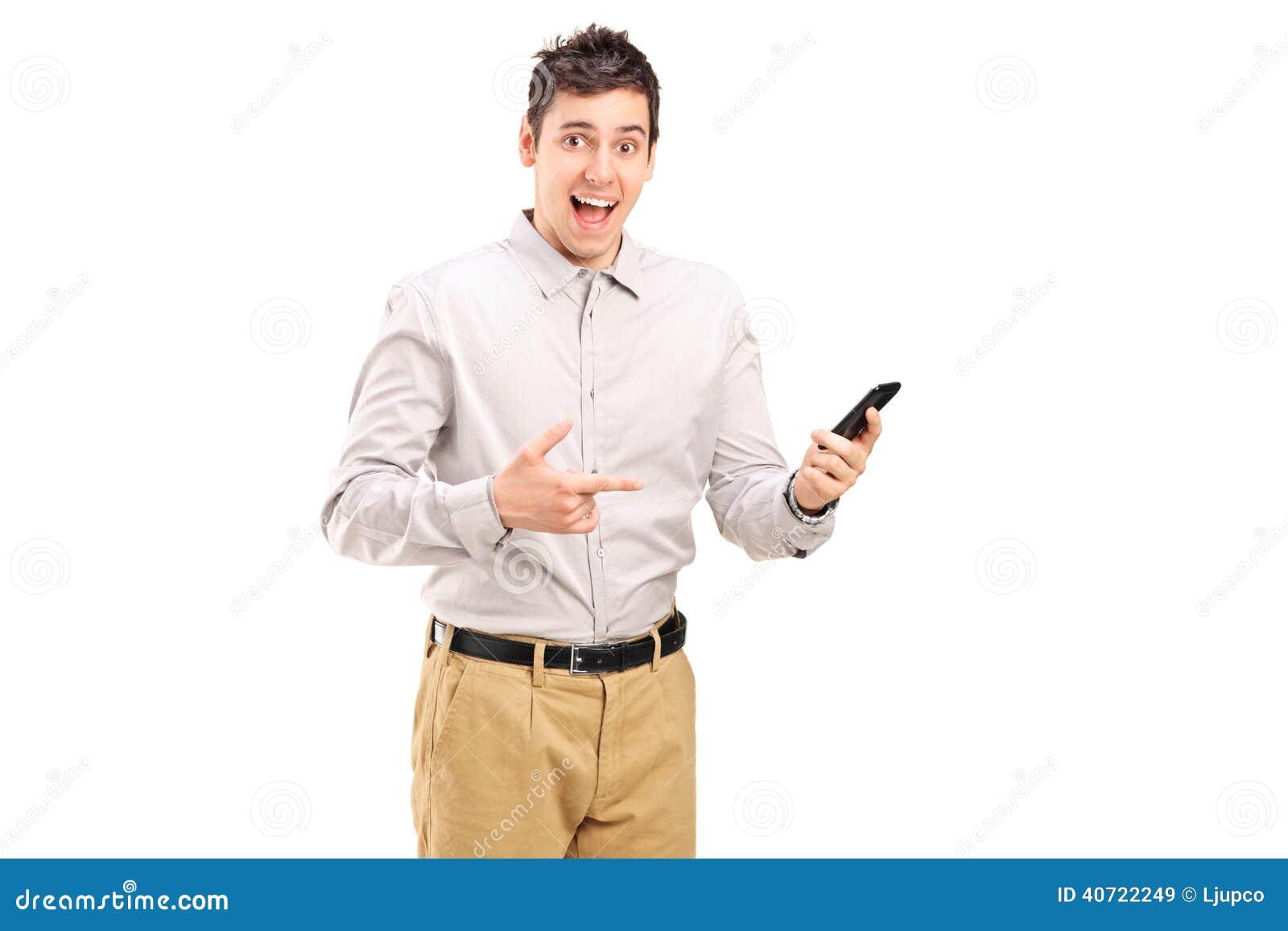 Aufgeregter junger Mann, der in Richtung zu einem Handy zeigt