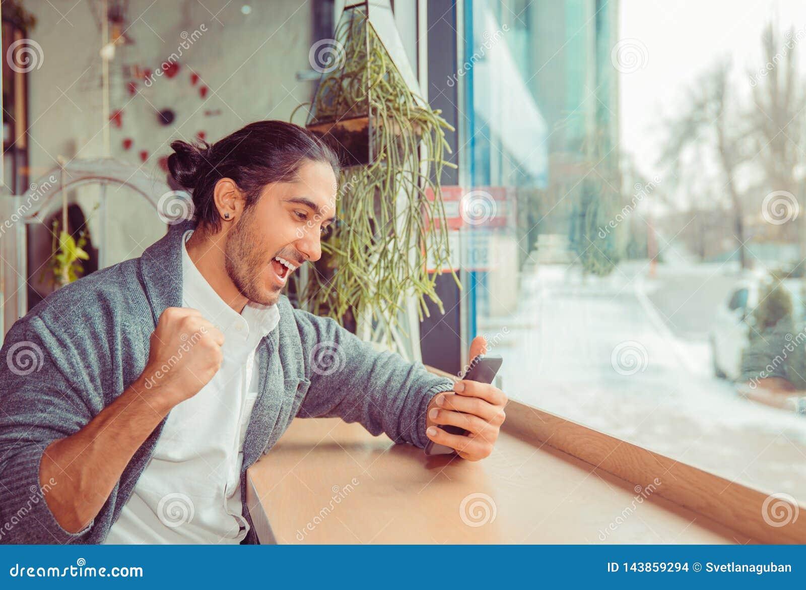 Aufgeregter Mann, der Nachrichten am intelligenten Telefon überprüft