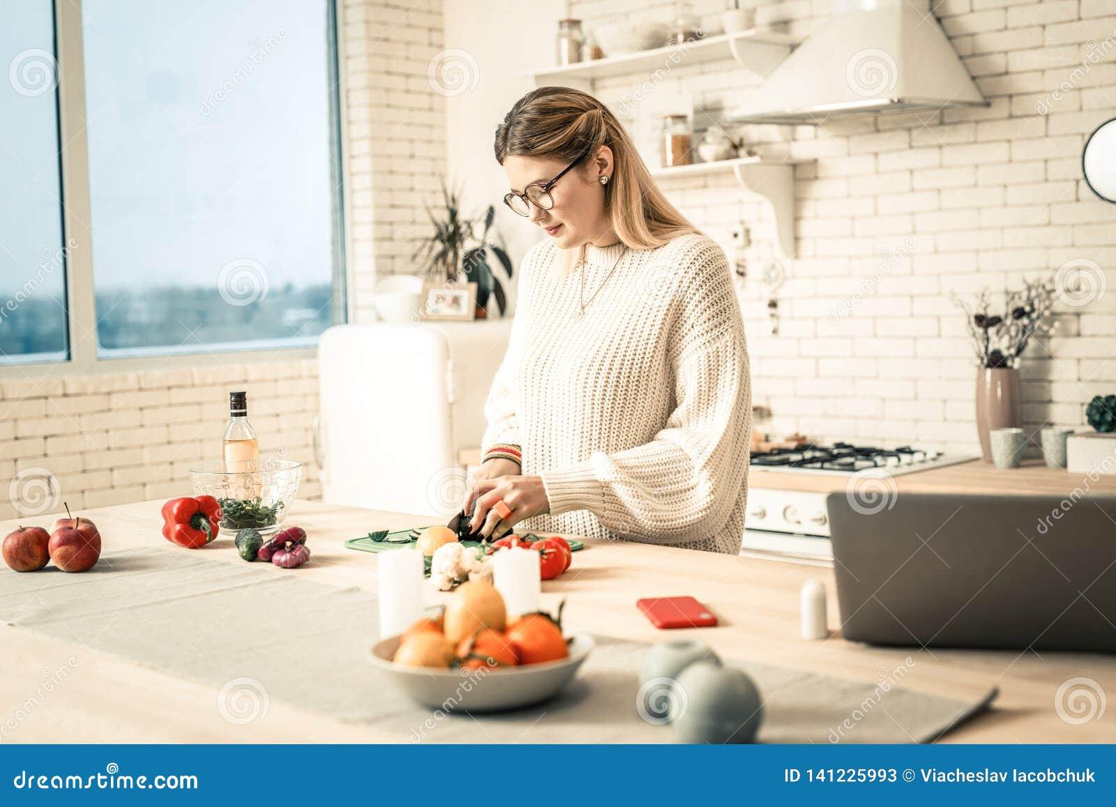 Aufmerksame fleißige Dame, die Gemüse während des Vorbereitungsprozesses schneidet
