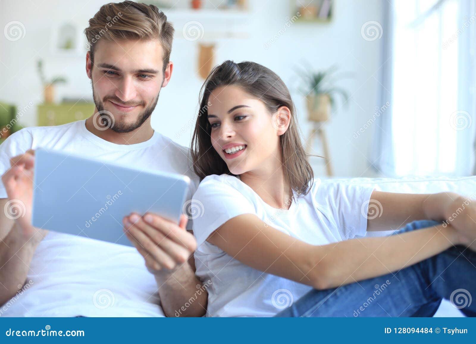 Aufpassende Medien der jungen Paare stellen online in einer Tablette zufrieden, die auf einem Sofa im Wohnzimmer sitzt