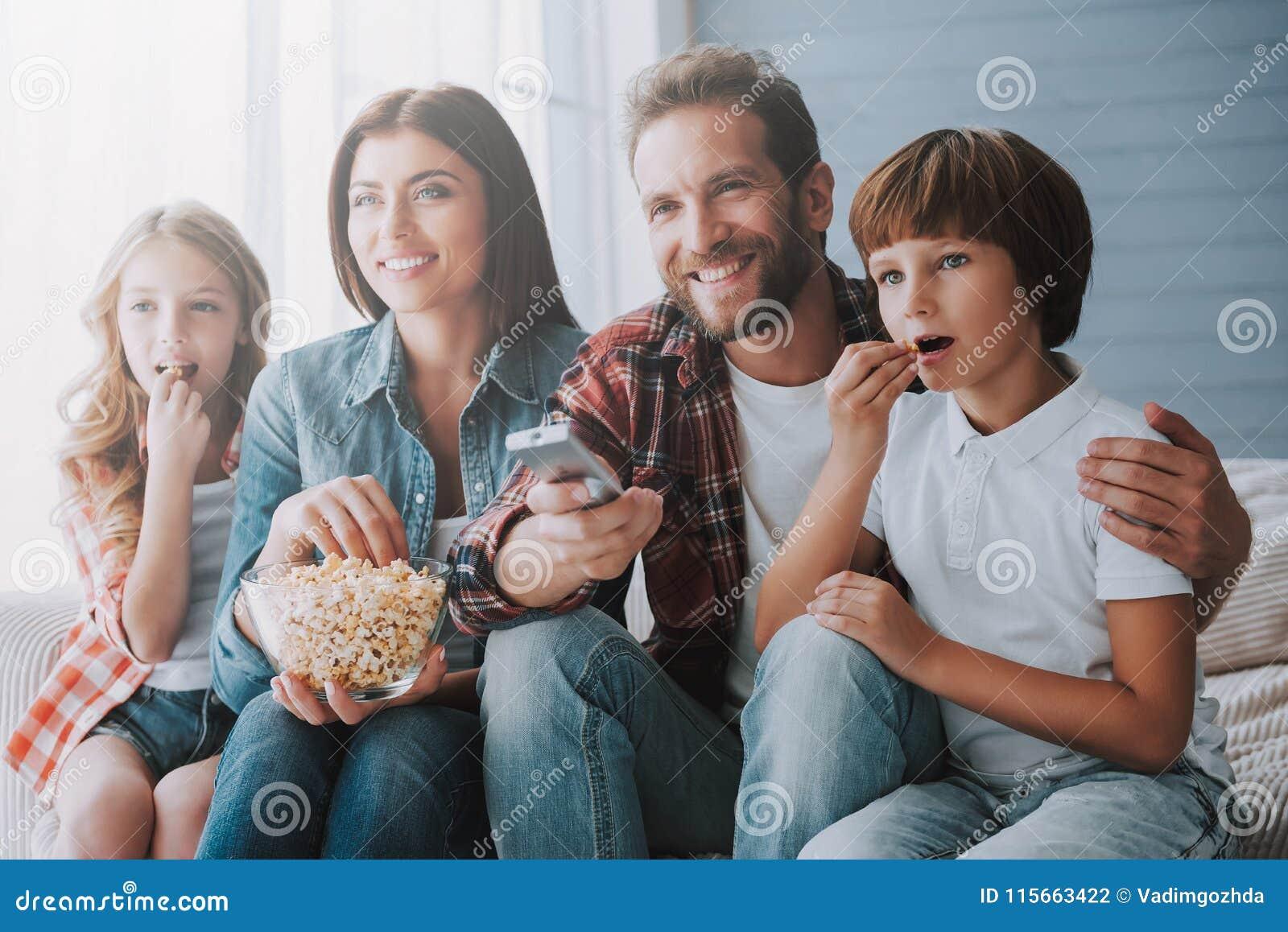 Aufpassender Film der glücklichen Familie zusammen und Popcorn essend während zu Hause